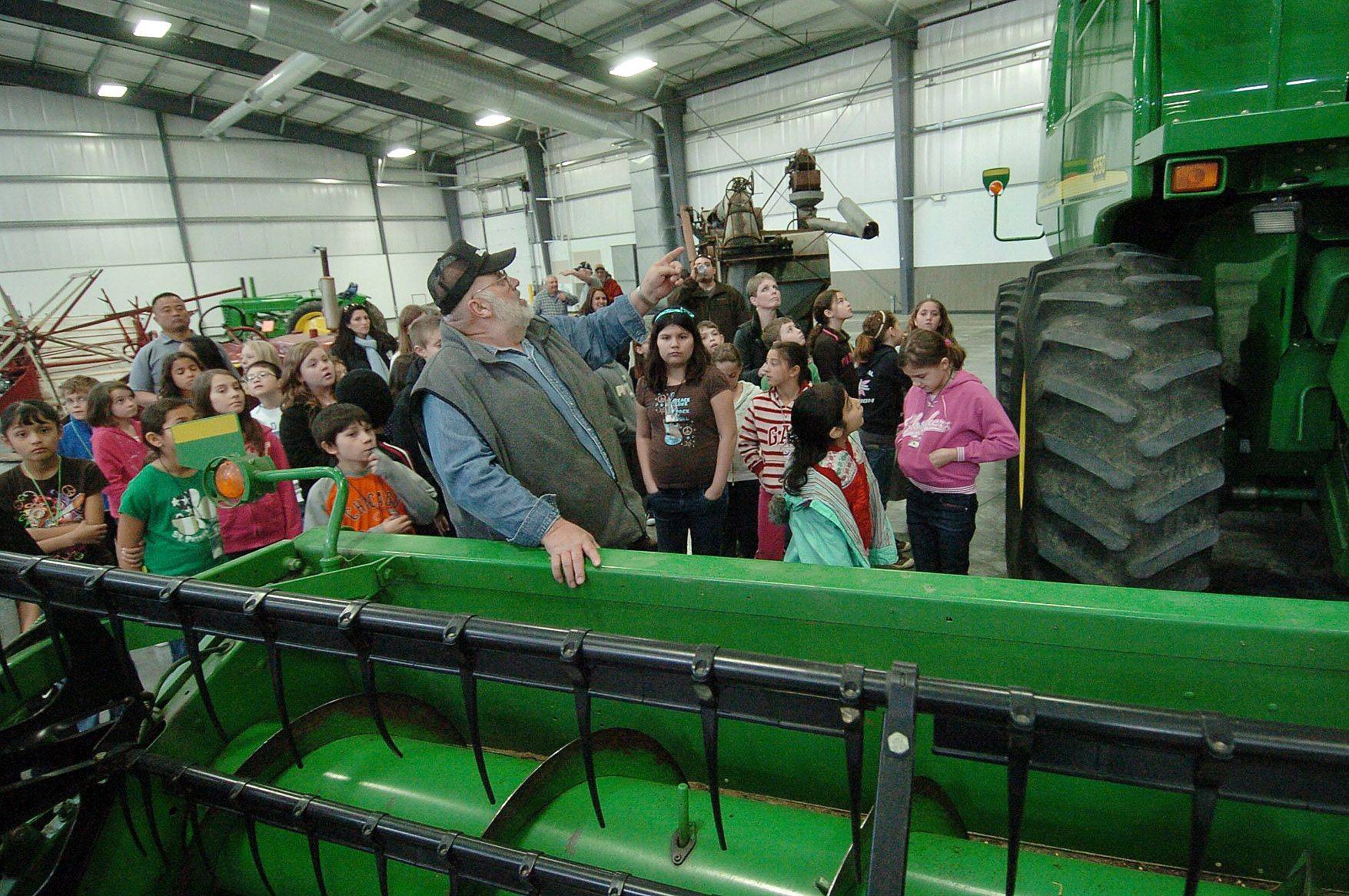 Ken Tekampe, left, of the Lake County Farm Heritage Association explains how a combine works to fourth graders from Big Hollow Elementary School in Ingleside at an Ag Expo at the Lake County Fairgrounds.