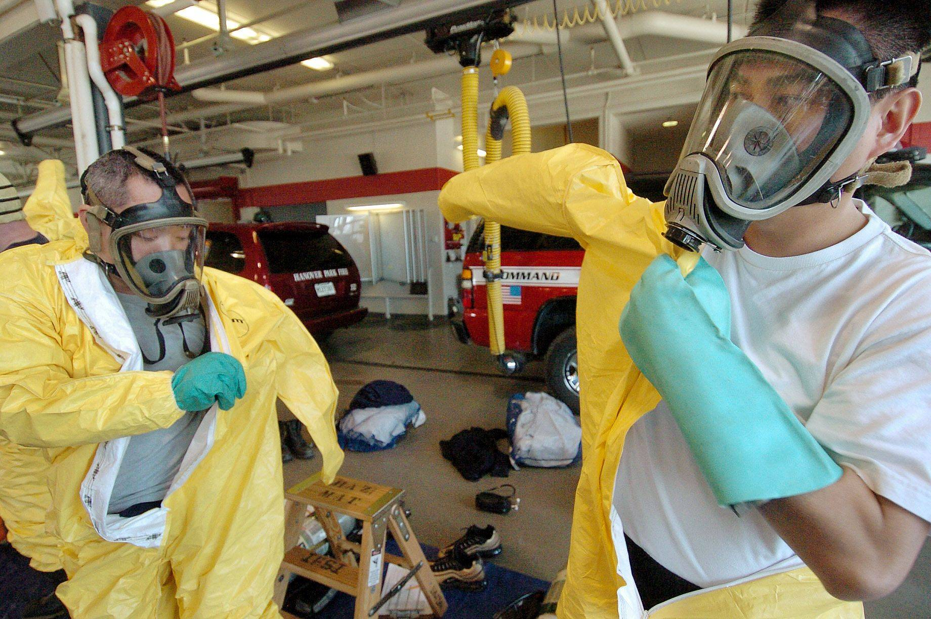 Visiting Hong Kong firefighters Ricky Chan, left, and Daniel Chan suit up in their haz-mat gear for a special training session at the Hanover Park Fire Department.