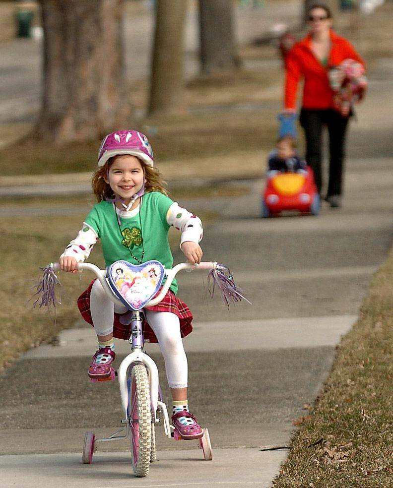 Five-year-old Clara Gradek rides her bike ahead of her mom Mairin Gradek and brother Oliver on a warm St. Patrick's Day in Arlington Heights.