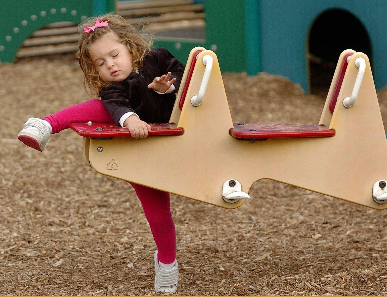 Two-year-old Reese Ginsberg struggles to climb aboard a teeter-totter in Virginia Terrace Park in Arlington Heights on an unseasonably-warm St. Patrick's Day.