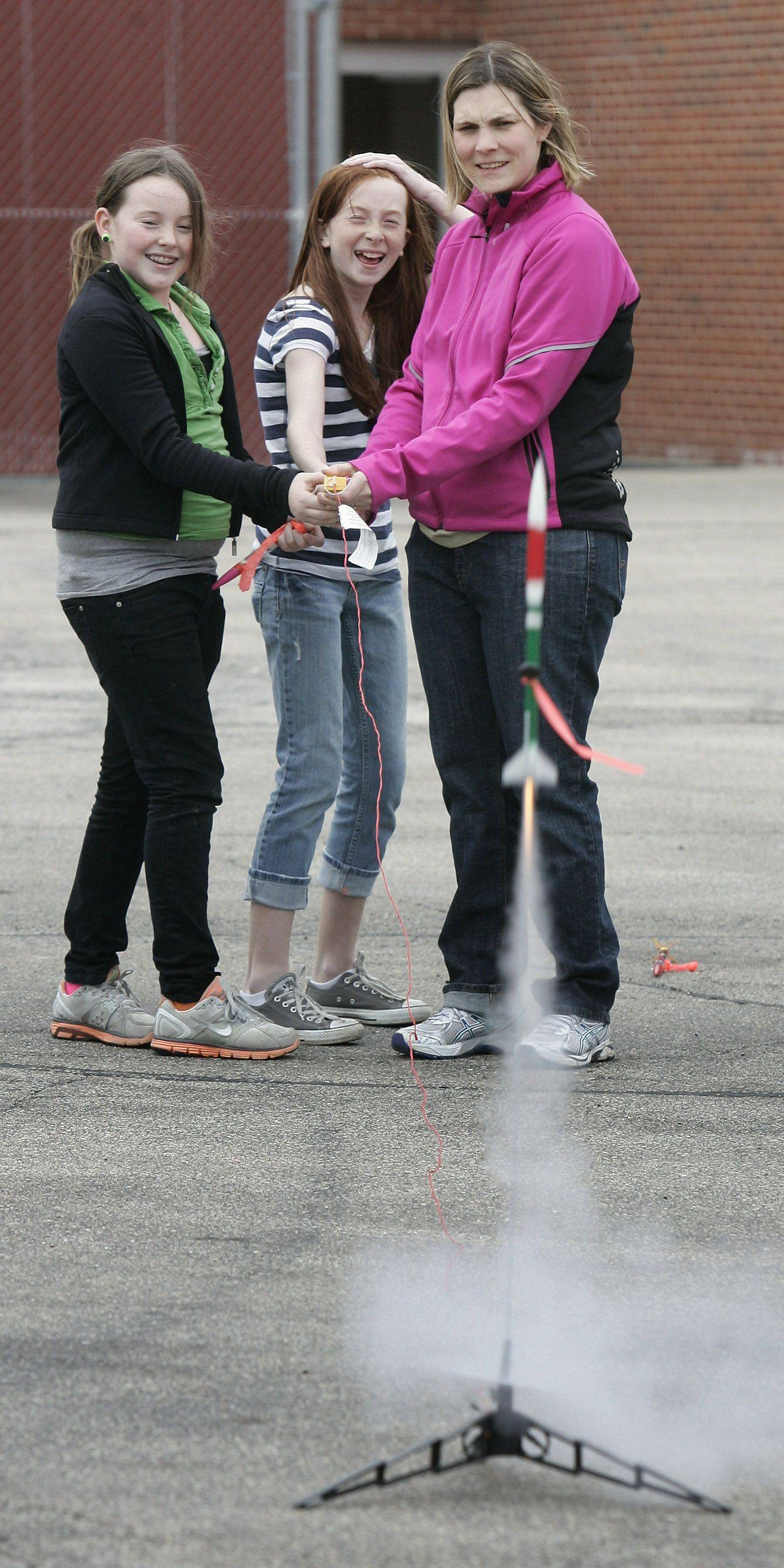 Abbie Sise, left, MacKenzie Linane, and science teacher Emily Loerraker watch the liftoff of Linane's rocket during the launch of handmade rockets at Fremont Middle School in Mundelein.