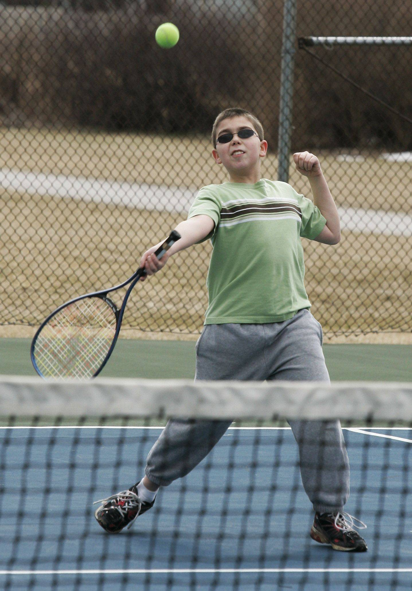Sammy Thornburg, 11, of Mundelein plays tennis with his father, Chris, as they enjoy the warmer weather Sunday at Maurice Noll Park in Mundelein.