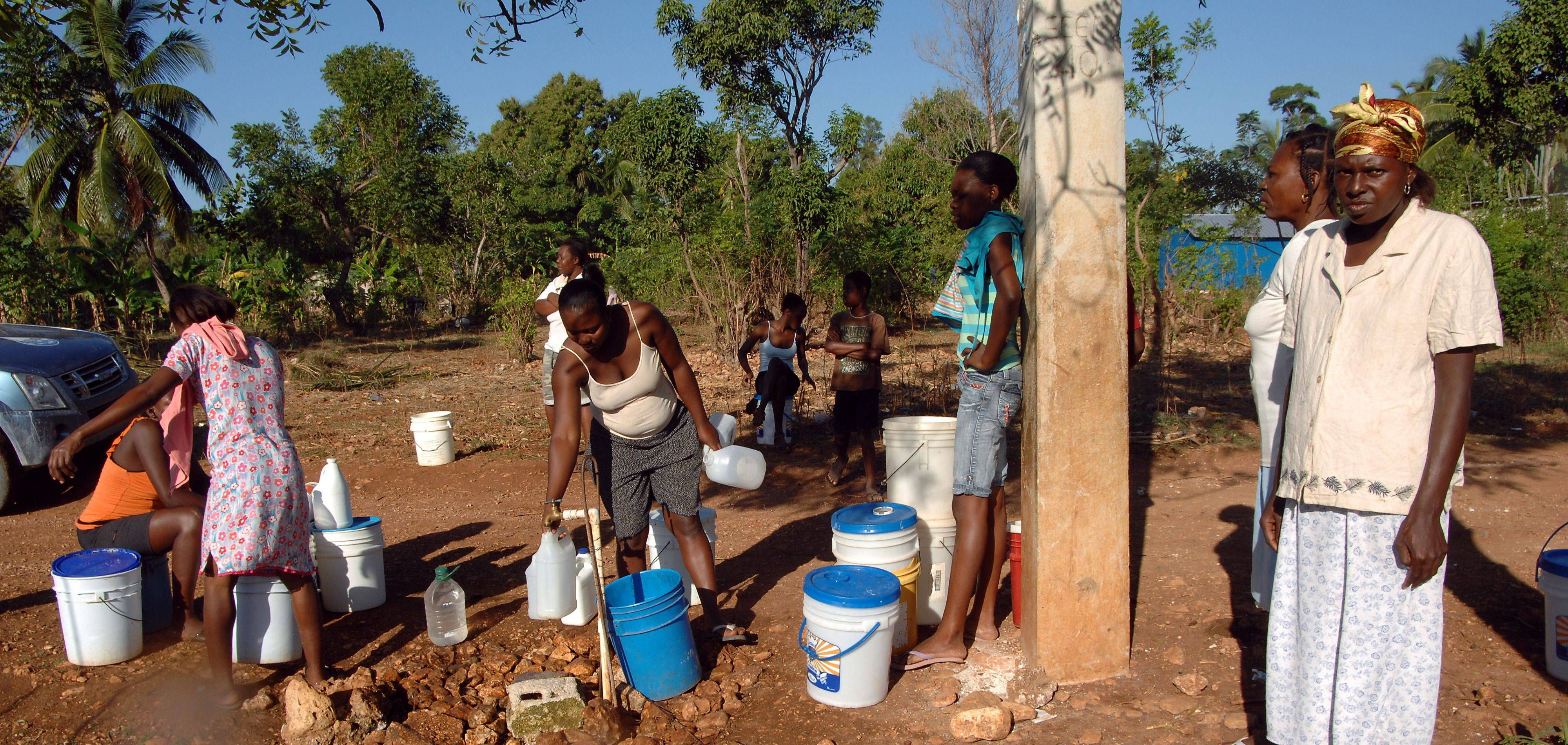 Haitian women gather at the only well for miles around to get their water supply for cooking, drinking and washing clothes. The well tested positive for the E-Coli bacteria.