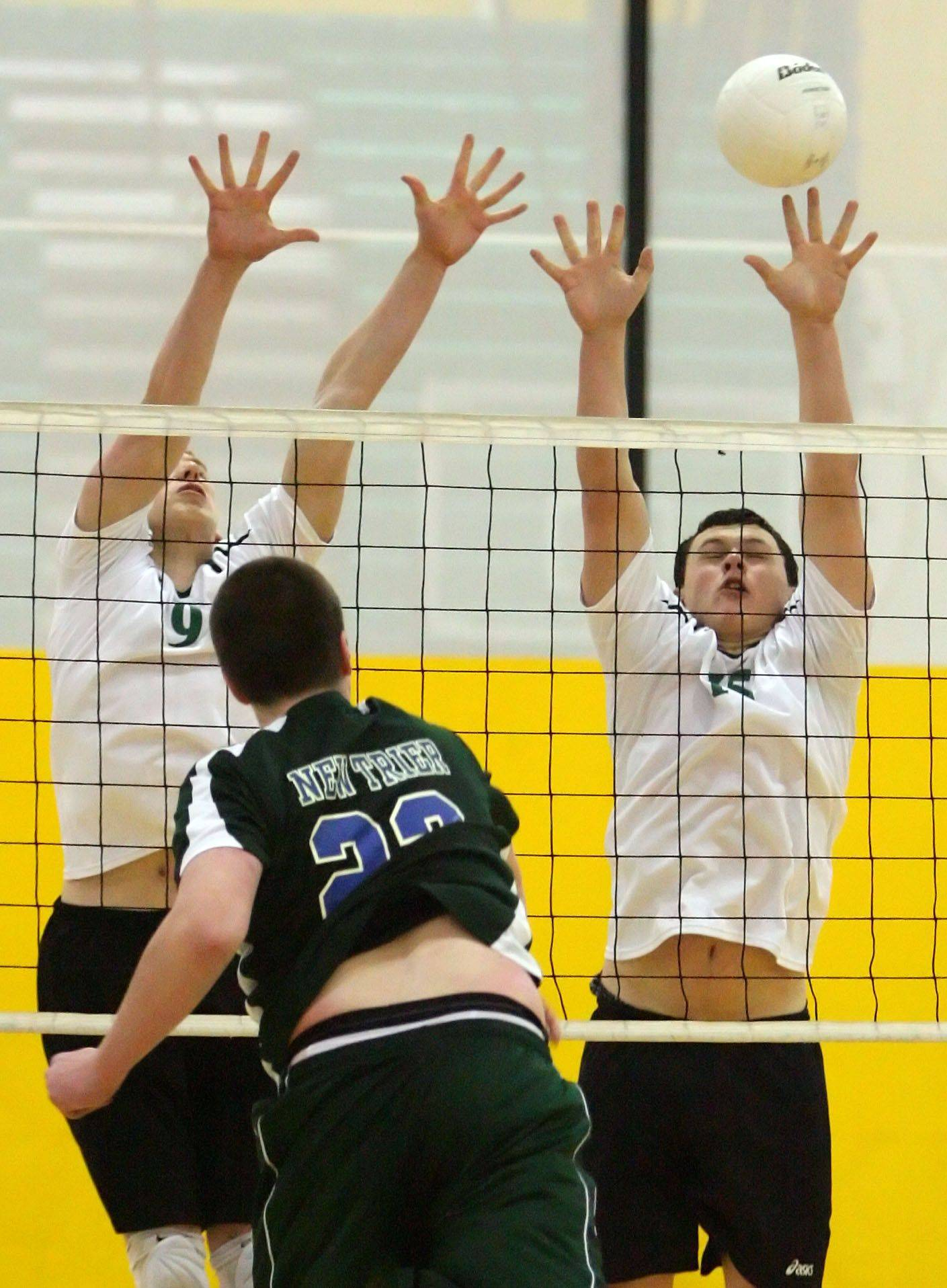 Stevenson's Jason Fleischman, left, and Mitch Robinson go up to block the spike of New Trier's Andy Gates during their game Tuesday night at Stevenson.