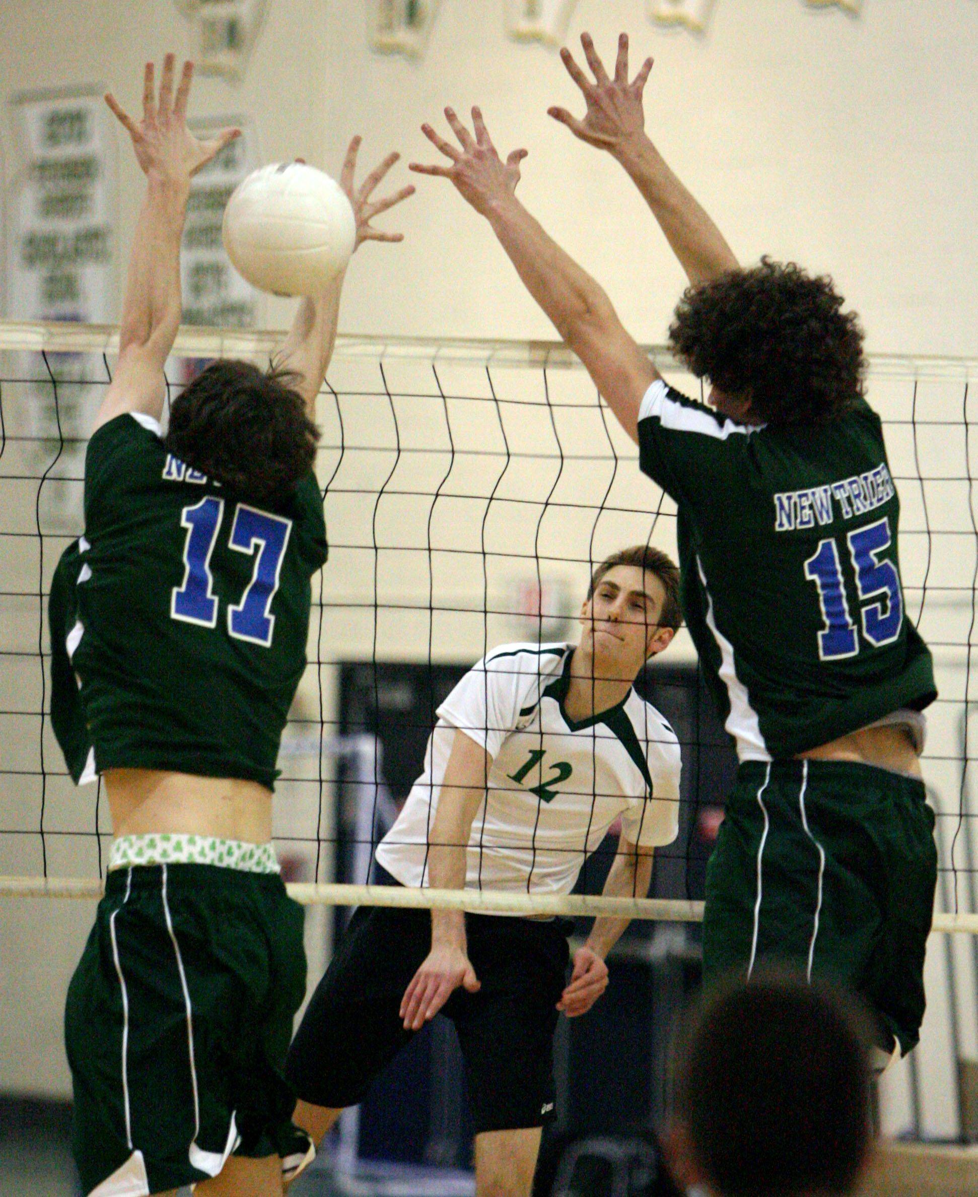 Stevenson's Danny Gescheidle spikes one past New Trier's Eric Smith, left, and Jesse Solomon on Tuesday night at Stevenson.