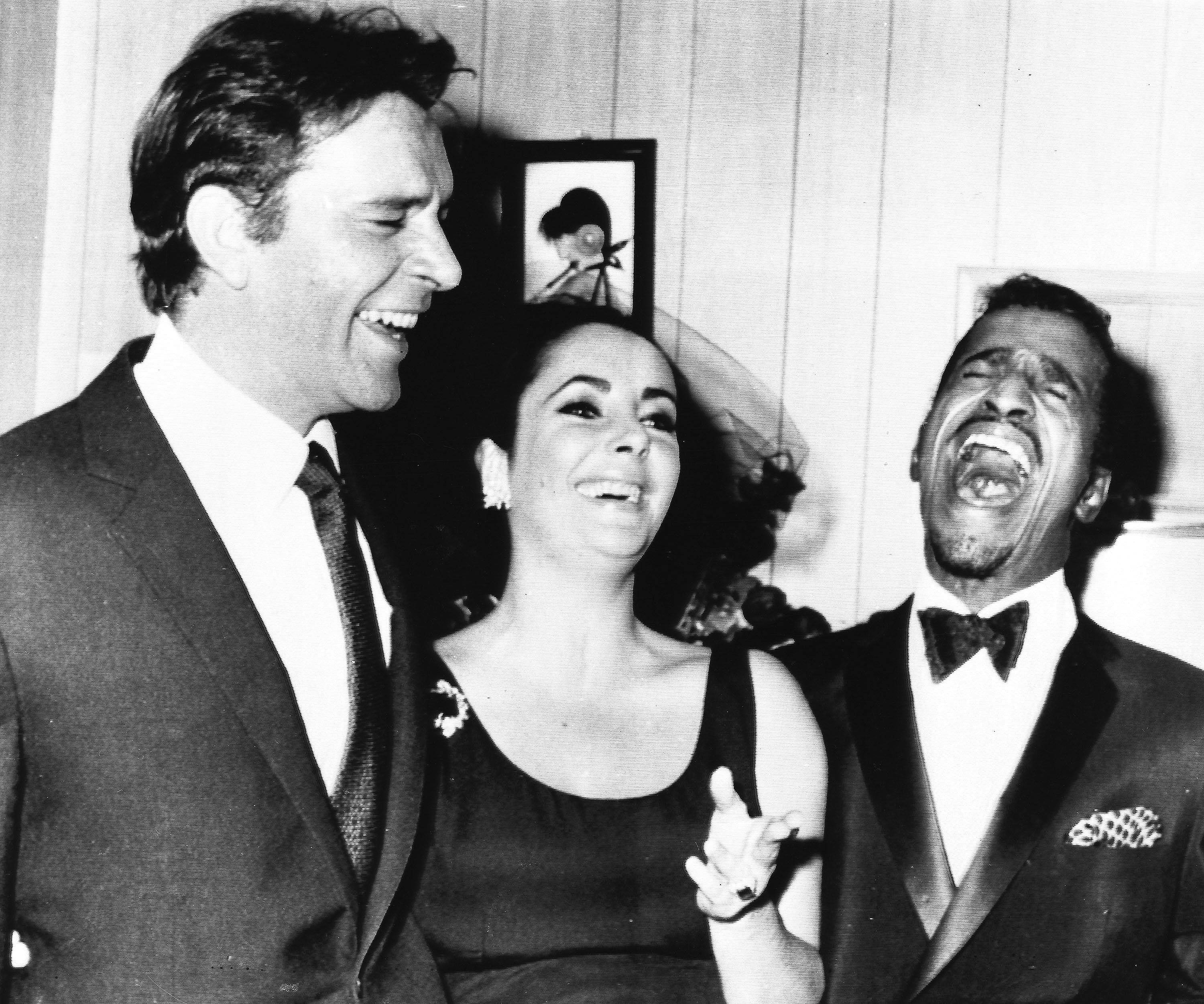 Elizabeth Taylor and husband Richard Burton share a joke with U.S entertainer Sammy Davis Jr., in Davis' dressing room after his opening at New York's Copacabana nightclub, April. 30, 1964.