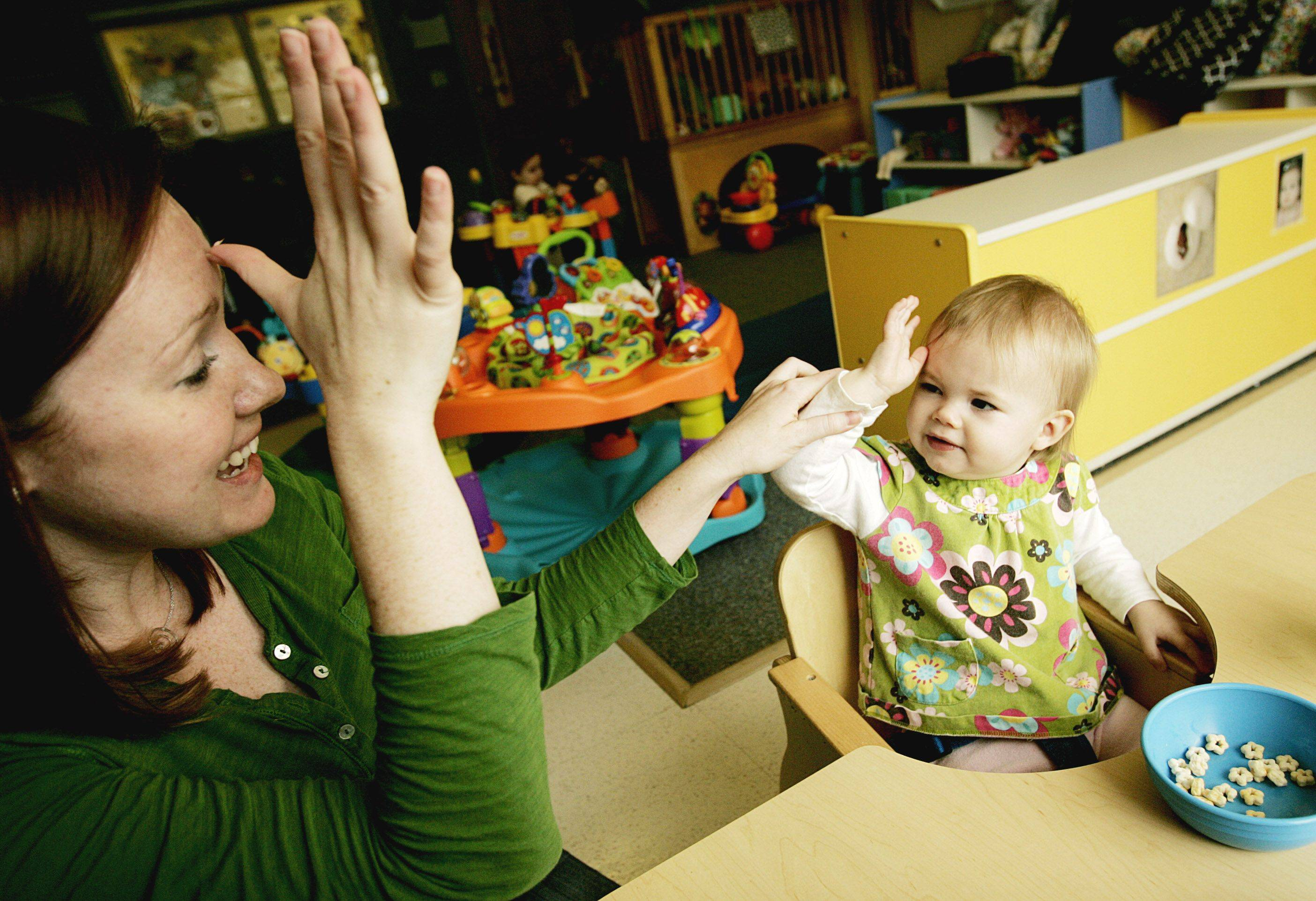 "Tanit JarusanChris Gillette teaches Camille ""Millie"" Buttimer how to say ""daddy"" in sign language at Lily Garden Child Care center in Villa Park."