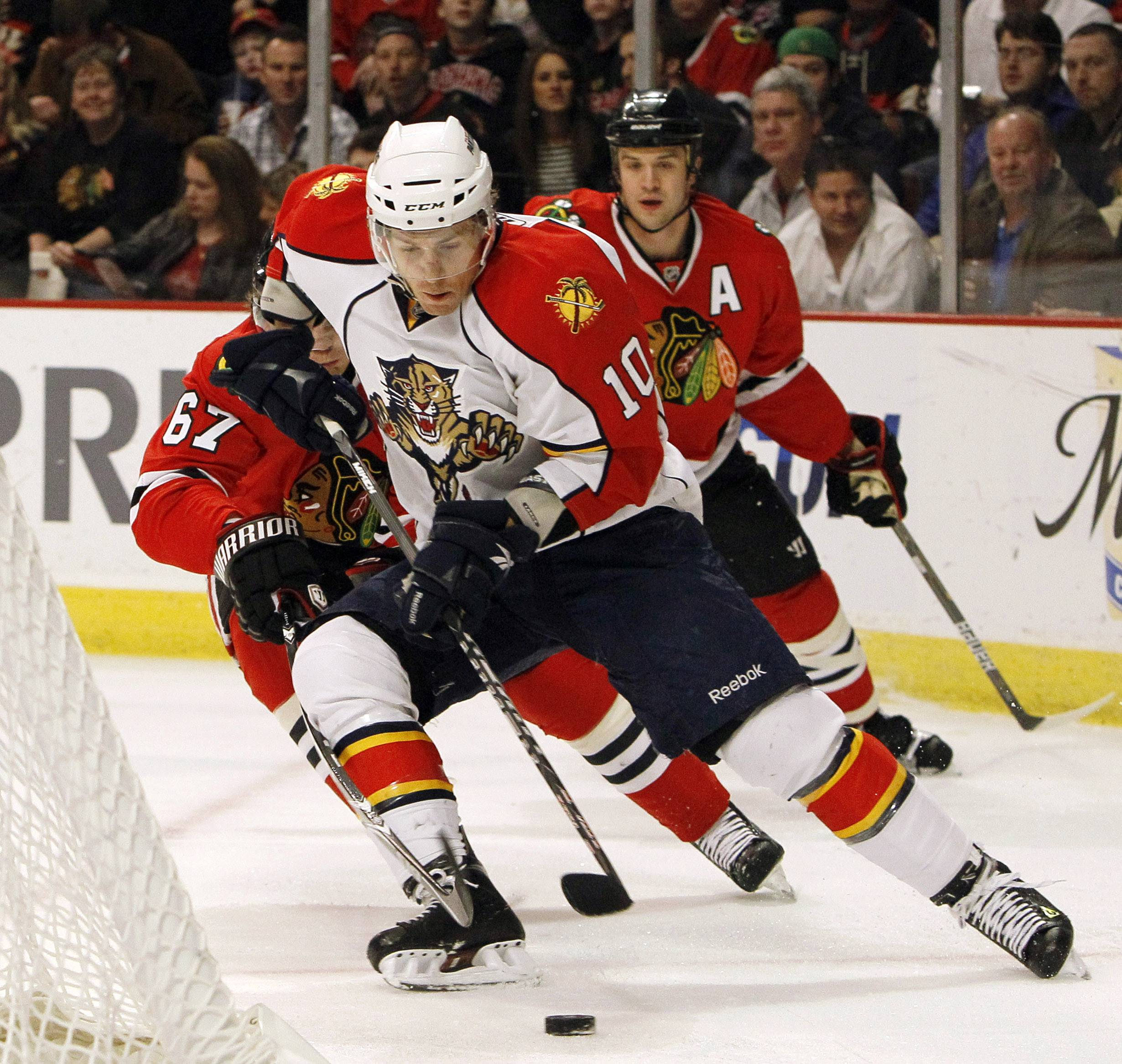 Florida Panthers left wing David Boothskates towards the net as Blackhawks center Michael Frolik, left, defends during the first period Wednesday. Hawks defenseman Brent Seabrook, background, looks on.