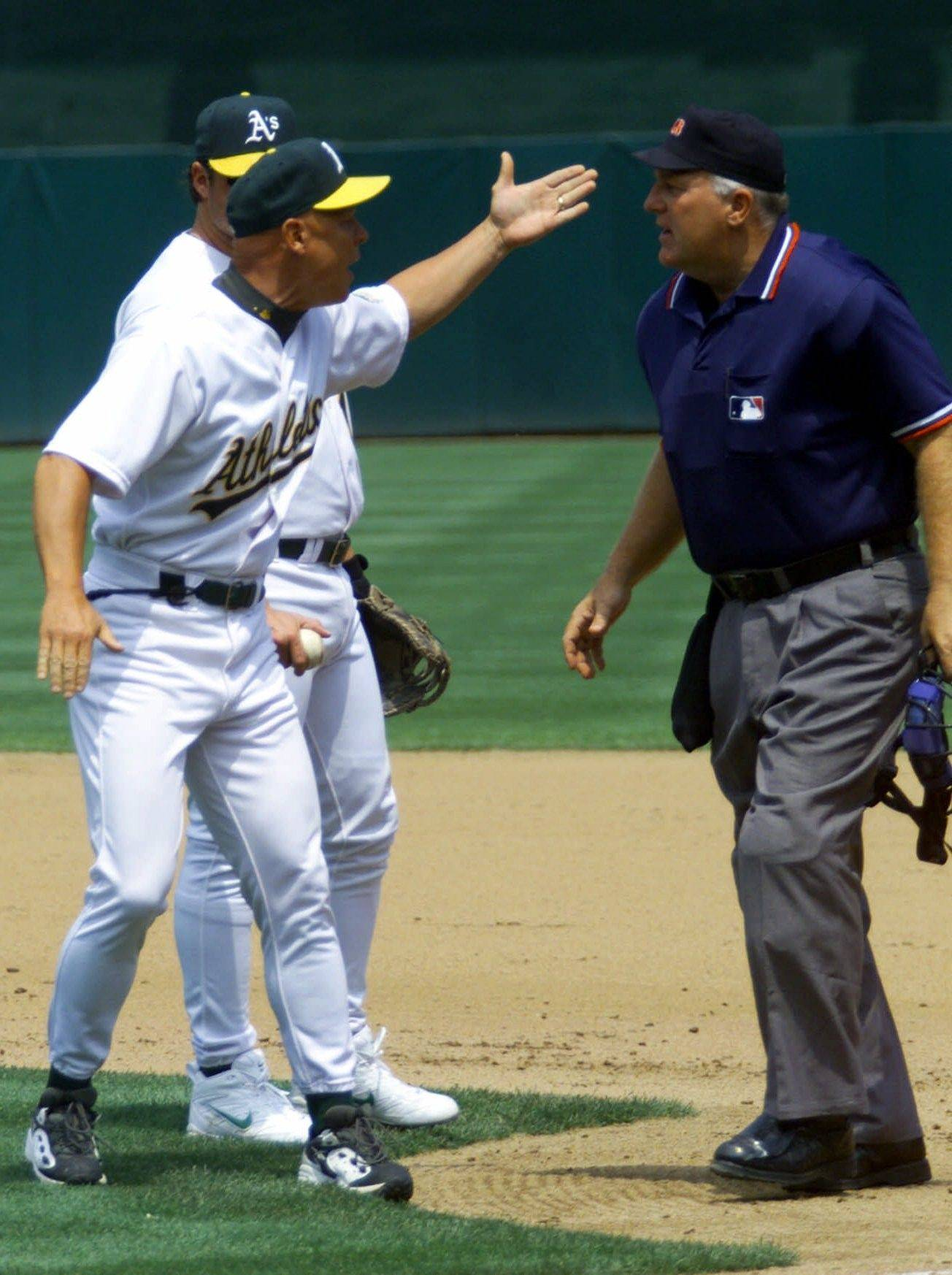 While with the Athletics as first-base coach in 2000, Mike Quade, left, argues with home-plate umpire Larry Young after being ejected from the game.