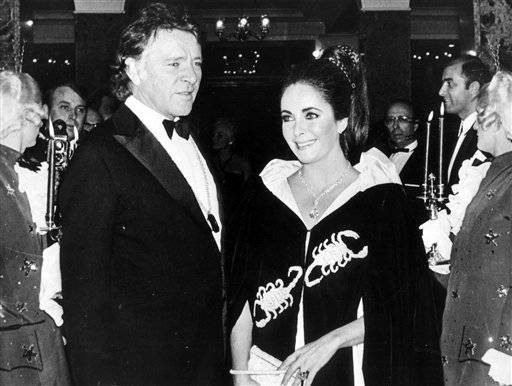 his Nov. 15, 1969 file photo shows Richard Burton and Elizabeth Taylor as they arrive at Hotel Hermitage for the Scorpion-Ball in Monaco. Princess Grace of Monaco invited the couple along with other guests for the celebration of her 40th birthday. Taylor is wearing the 69-carat diamond which is now known as the Taylor-Burton Diamond. Taylor died Wednesday at age 79 of congestive heart failure.