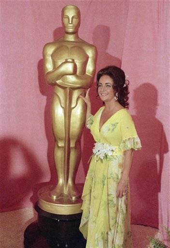 This April 2, 1974 file photo shows actress Elizabeth Taylor standing by a statue of the Academy Award Oscar in Los Angeles. Elizabeth Taylor had it all: the violet, almond-shaped eyes, the creamy skin, the pouty lips and raven hair. Of course, there were her Oscars, iconic roles and many husbands, too, but Taylor is indeed most renowned for her beauty.