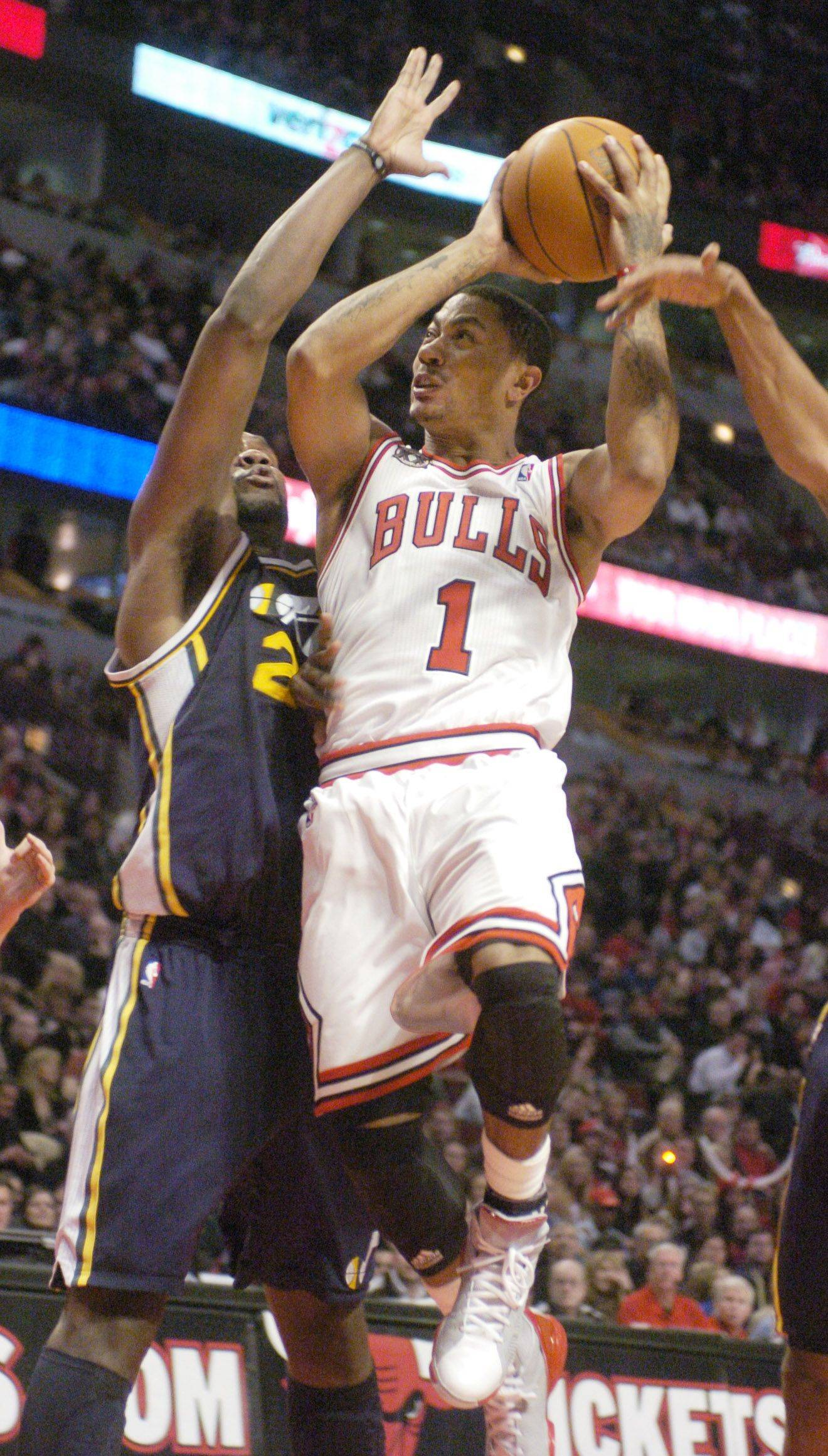 Derrick Rose of the Bulls drives to the basket against Al Jefferson of the Jazz.