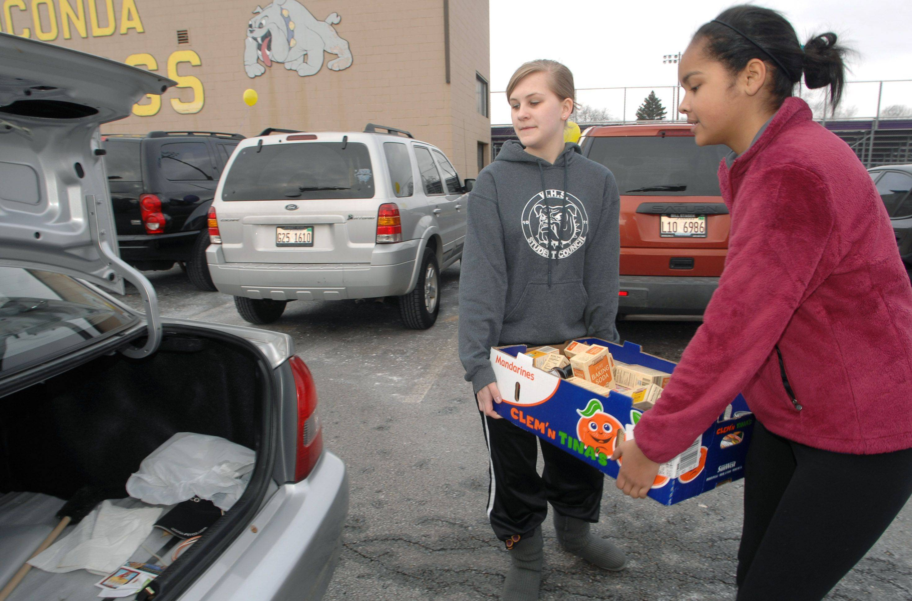 Wauconda High School sophomore student council members Sami Sroka, left, and Tatiana Moten load up vehicles Friday morning as part of the school's food drive for the Wauconda-Island Lake Food Pantry.