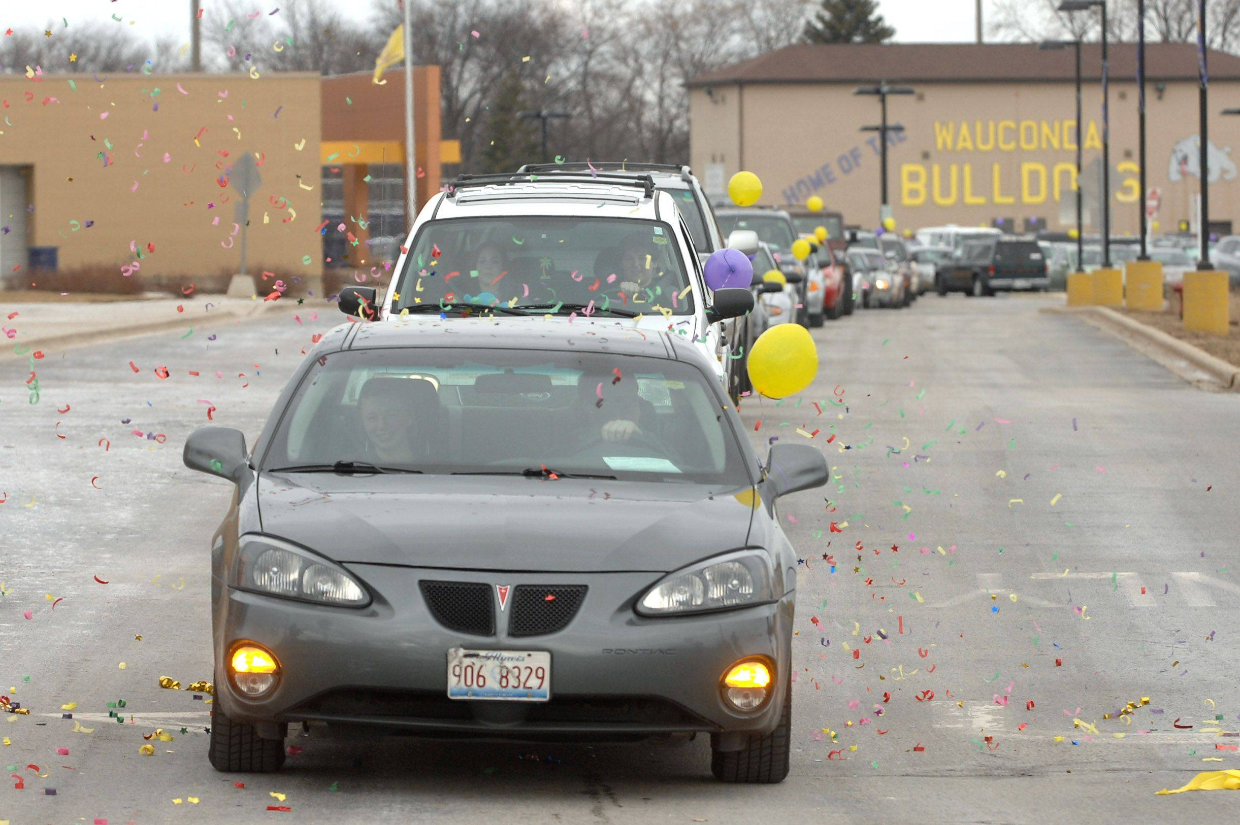 The vehicle procession carrying food to the Wauconda-Island Lake Food Pantry leaves Wauconda High School Friday morning. Students collected more than 2,100 items as part of their annual food drive.