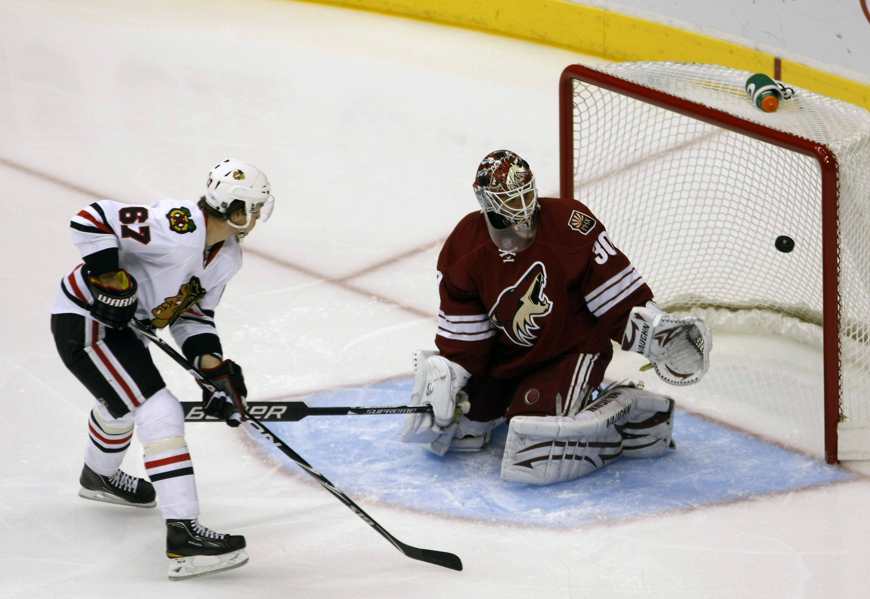 Chicago Blackhawks center Michael Frolik, left, of Czechoslovakia, shoots on Phoenix Coyotes goalie Ilya Bryzgalov of Russia, during the first period of an NHL hockey game on Sunday, March 20, 2011, in Glendale, Ariz.