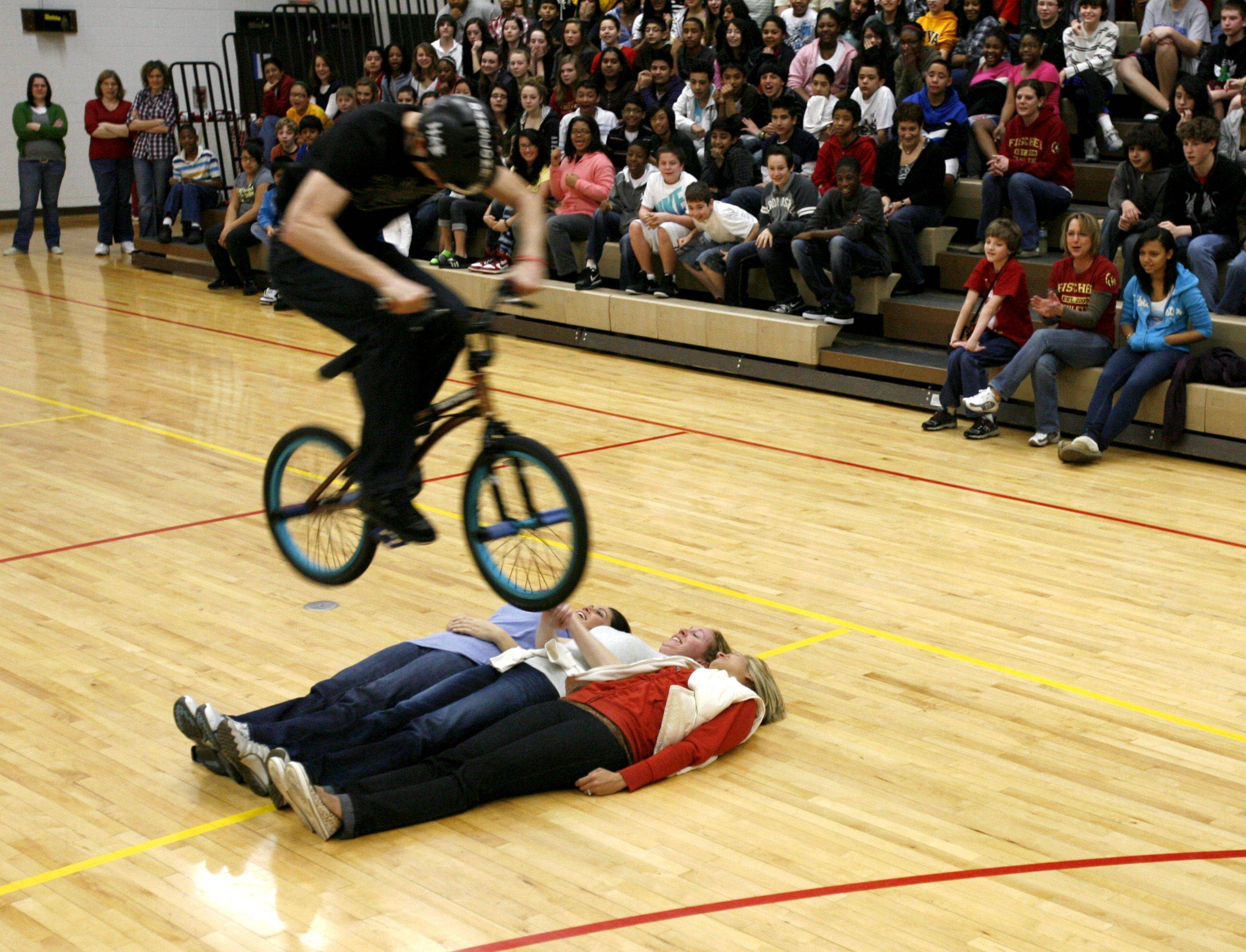 Fischer Middle School students, in Aurora, receive a visit from X-Games and Pro BMX rider Matt Wilhelm, who performed for students and delivered messages in perseverance, overcoming odds and bullying. Above, Wilhelm jumps over teachers Jennifer Klen, Melissa Cullo and Michelle Nalon.