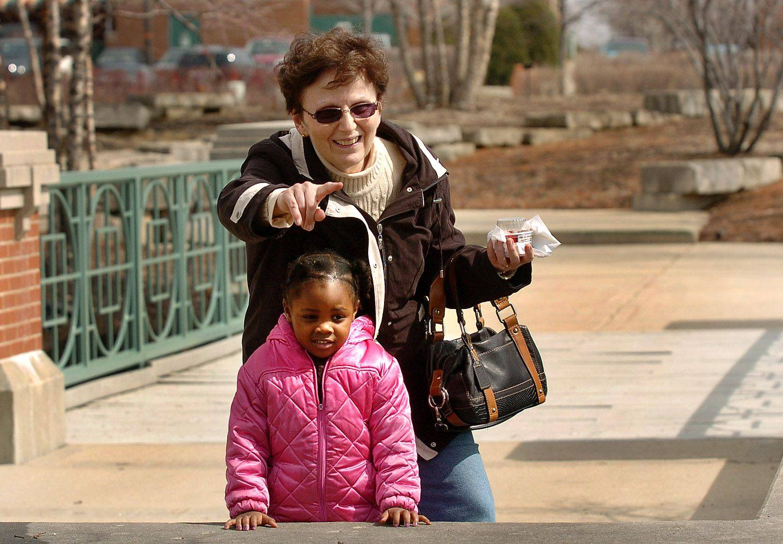 Carolyn Scutella takes an afternoon stroll with 4-year-old Melyssa Muwanga in search of ducks in the Town Square pond next to the Schaumburg library.