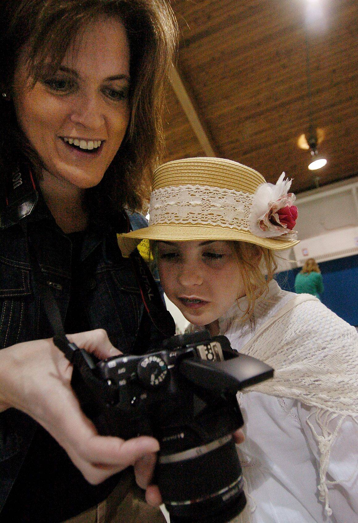 Volunteer mom Carrie Greene shows her daughter Ruby, dressed in Victorian style, pictures she has taken during The Chicago Fair, a social science simulation put on by third grade students at Half Day School in Lincolnshire.