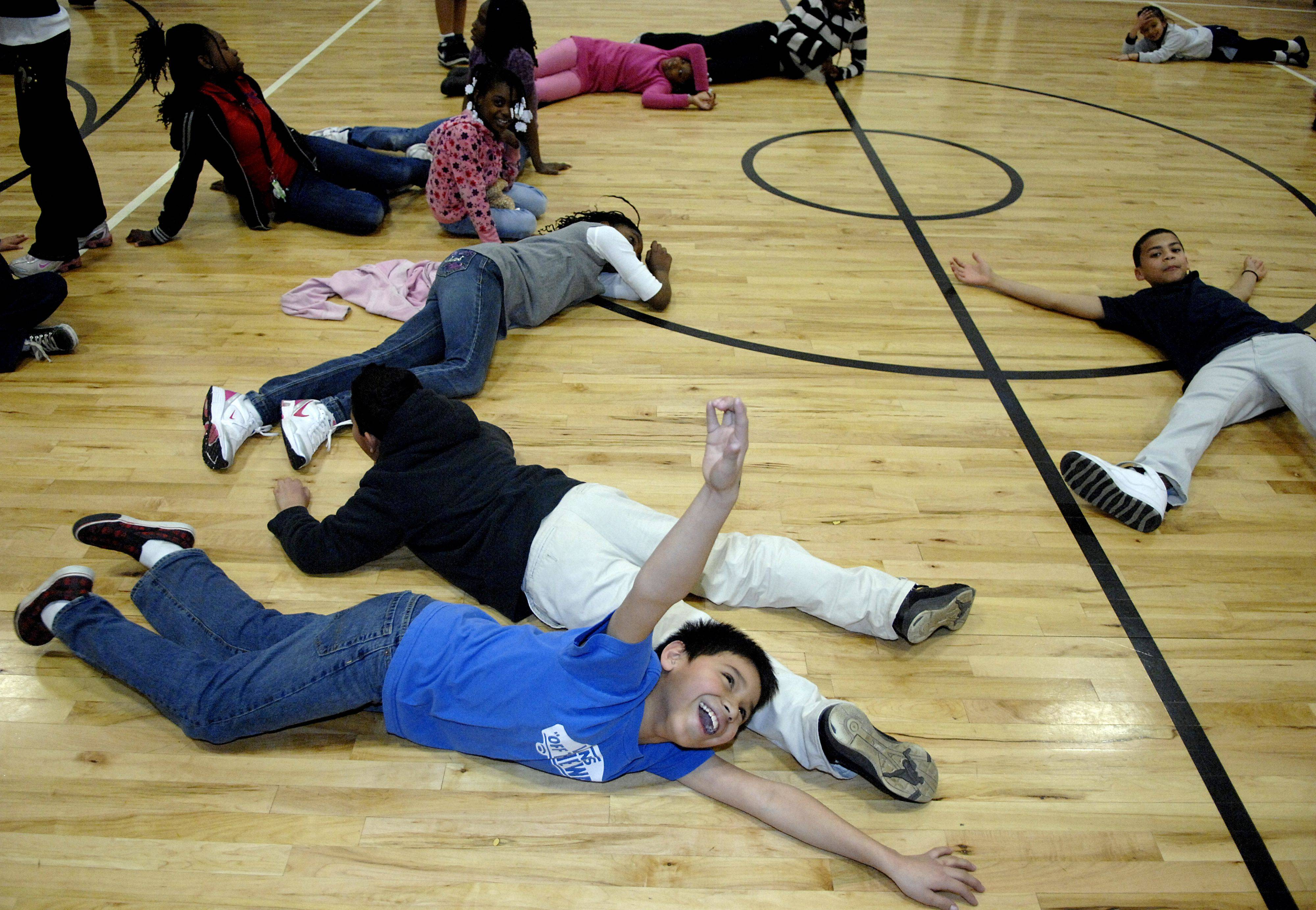 Eduardo Perez, 9, of Elgin, makes a dramatic scene with others at the Boys and Girls Club of Elgin after participating in a Guinness Book of World Records attempt to break the current record for most people doing jumping jacks at the same time on Tuesday, March 22. Dozens of kids participated in the 2-minute challenge and were wiped out afterwards.