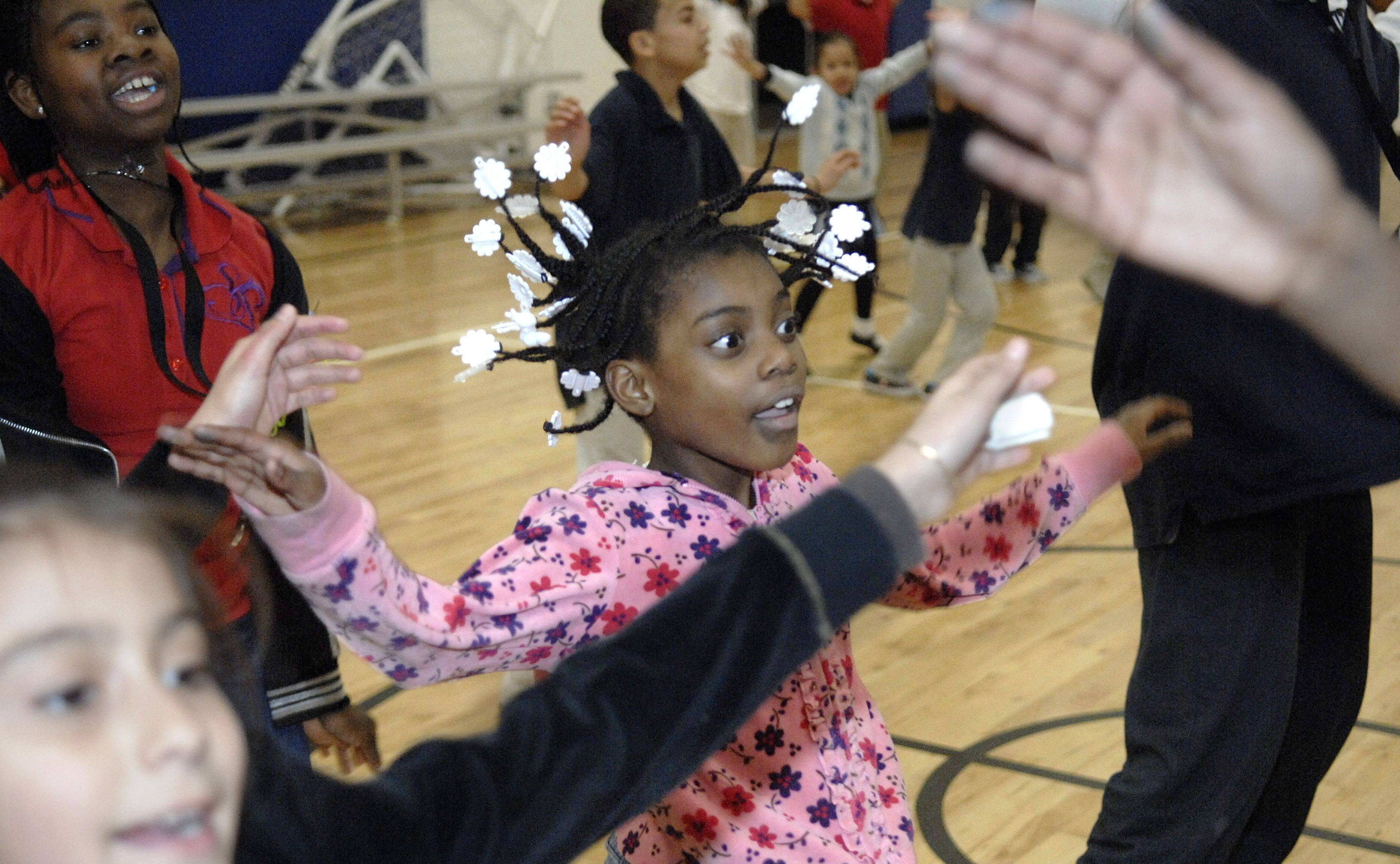 Adrianna Jackson's hair flies while she participates in a Guinness Book of World Records attempt to break the current record for most people doing jumping jacks at the same time at the Boys and Girls Club of Elgin. Adrianna, 8, of Elgin and dozens of kids participated in the 2-minute challenge, and jumped at 5:30 along with other clubs across the country on Tuesday.