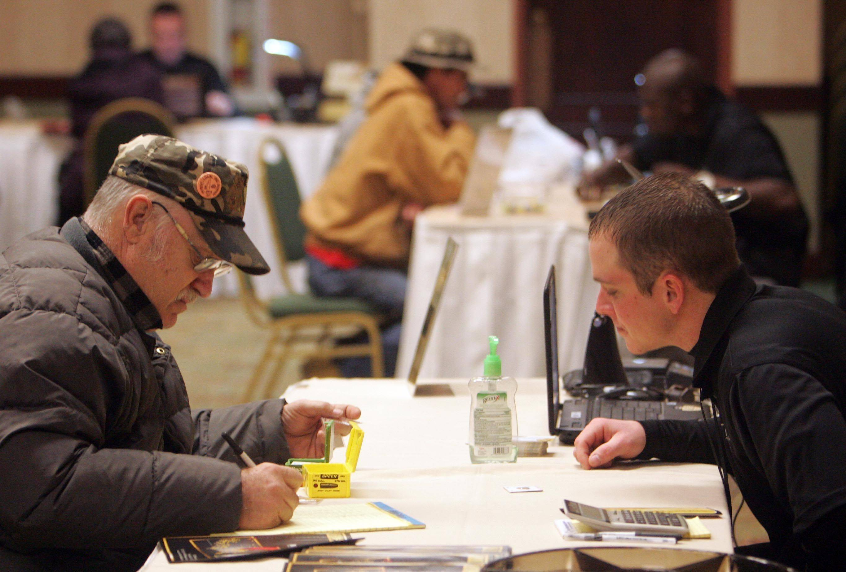 Coin collector Rich Carlsen of Gilberts, left, discusses the value of his coins with buyer Nick Wittman during the International Coin Collectors Association Treasure Hunter show at the Elgin Holiday Inn Wednesday.