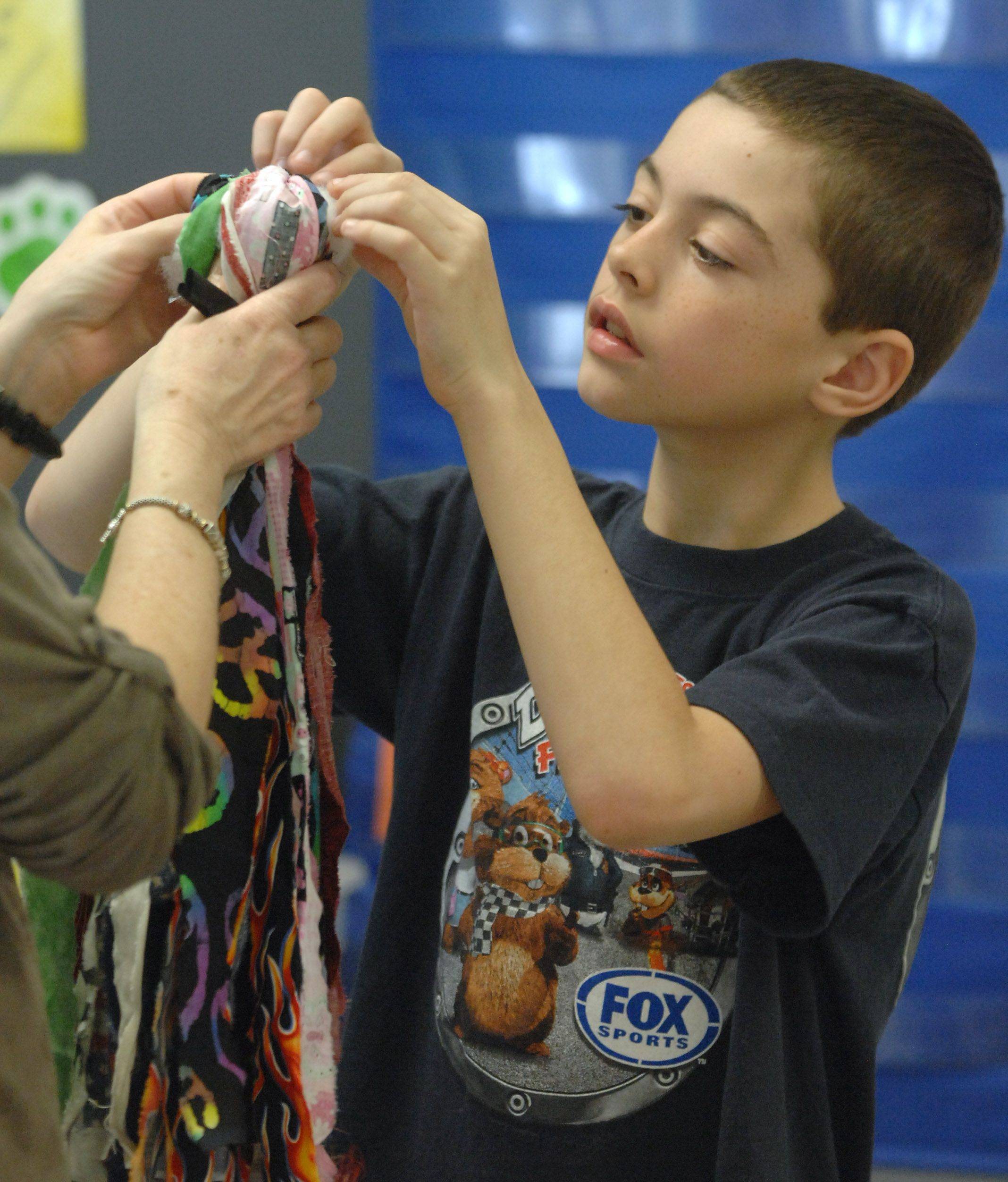 Third-grade students participating in Pioneer Day at Woodland Elementary East made rag dolls, which was one activity at their Gages Lake school. Breanden Zeitler puts the finishing touches on his doll Thursday.