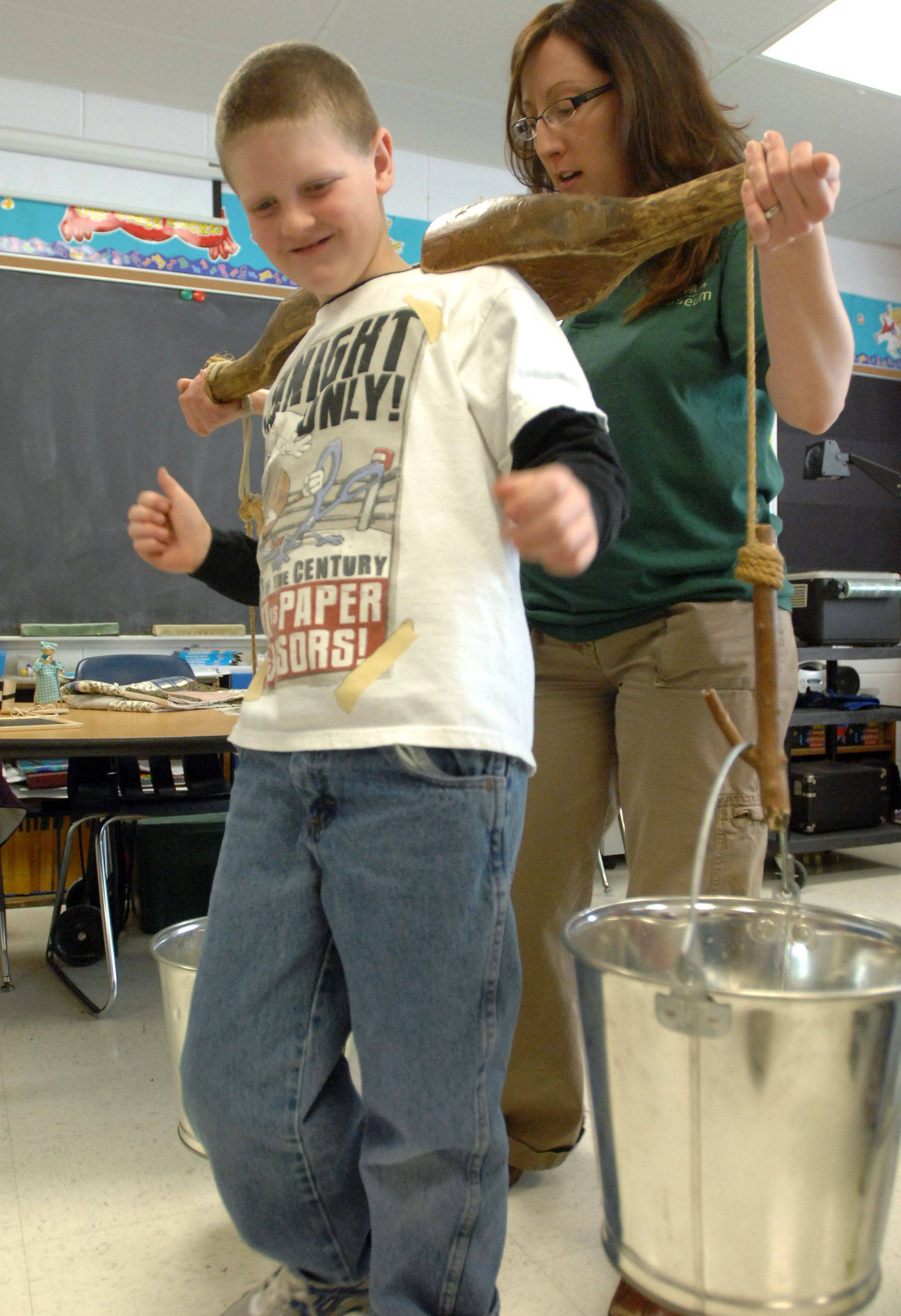 Lake County Discovery Museum educator Seleena Kuester shows Woodland Elementary East third grade student Owen Brown what it's like to use a yoke to carry buckets of water to Thursday in Gages Lake. Students from three classes participated in Pioneer Day rotating through various activities.