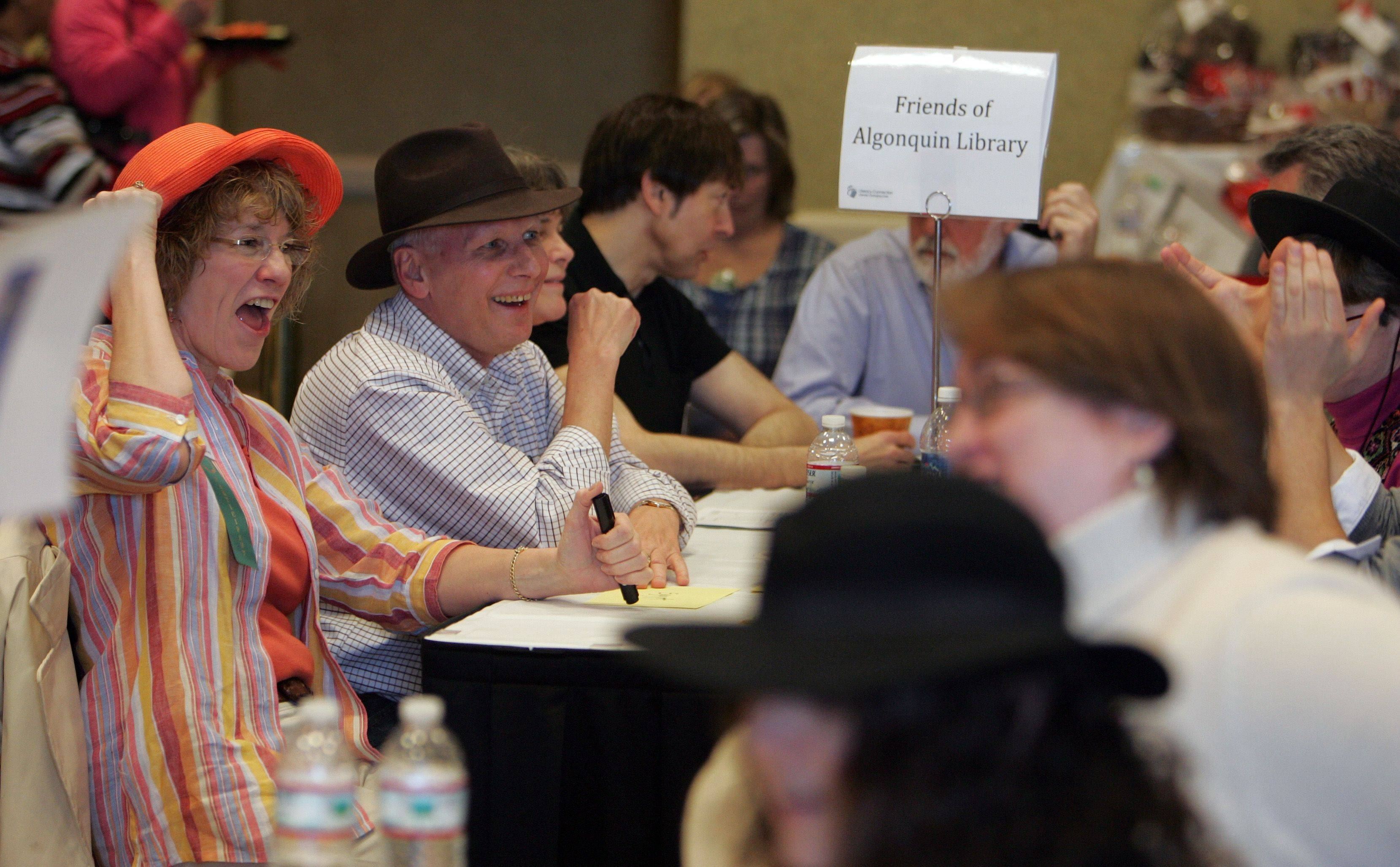 Virginia Freyre of the Friends of Algonquin Library group, left in orange hat, cheers after the team responded with the correct answer during the 14th-annual Trivia Bee presented by the Literacy Connection at the Grand Victoria Casino Saturday, March 19 in Elgin.