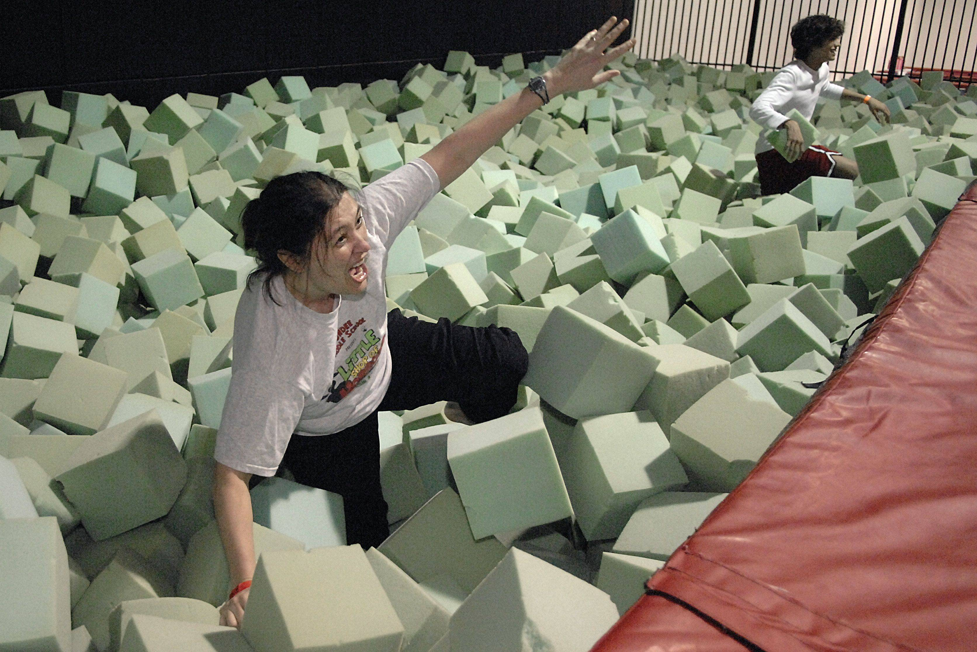 Dundee Middle School eighth grade resource teacher Ann Campbell digs her way out of a foam pit after jumping into via trampoline during the Bounce Out Cancer fundraiser at Xtreme Trampolines in Carol Stream on Friday, March 18.