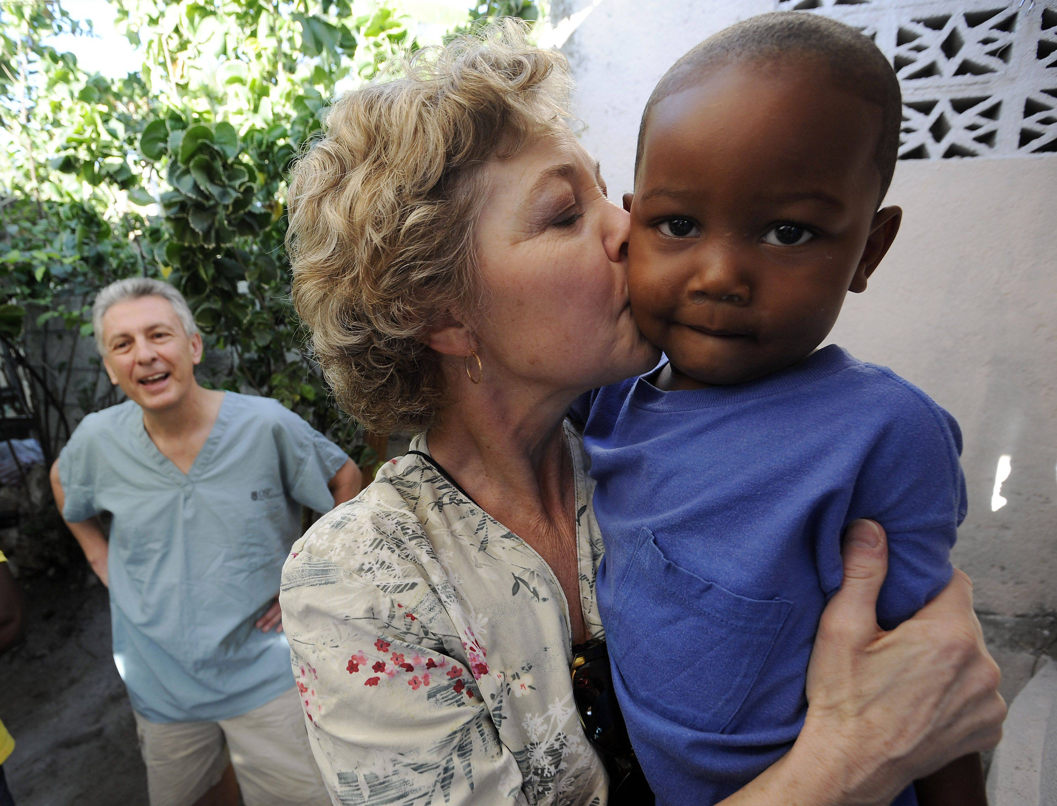 Trudy Vogel plants a big kiss on Godson as her husband, Paul looks on. Godson is their sponsored child who was pulled from the earthquake at his home in Jacmel, Haiti.