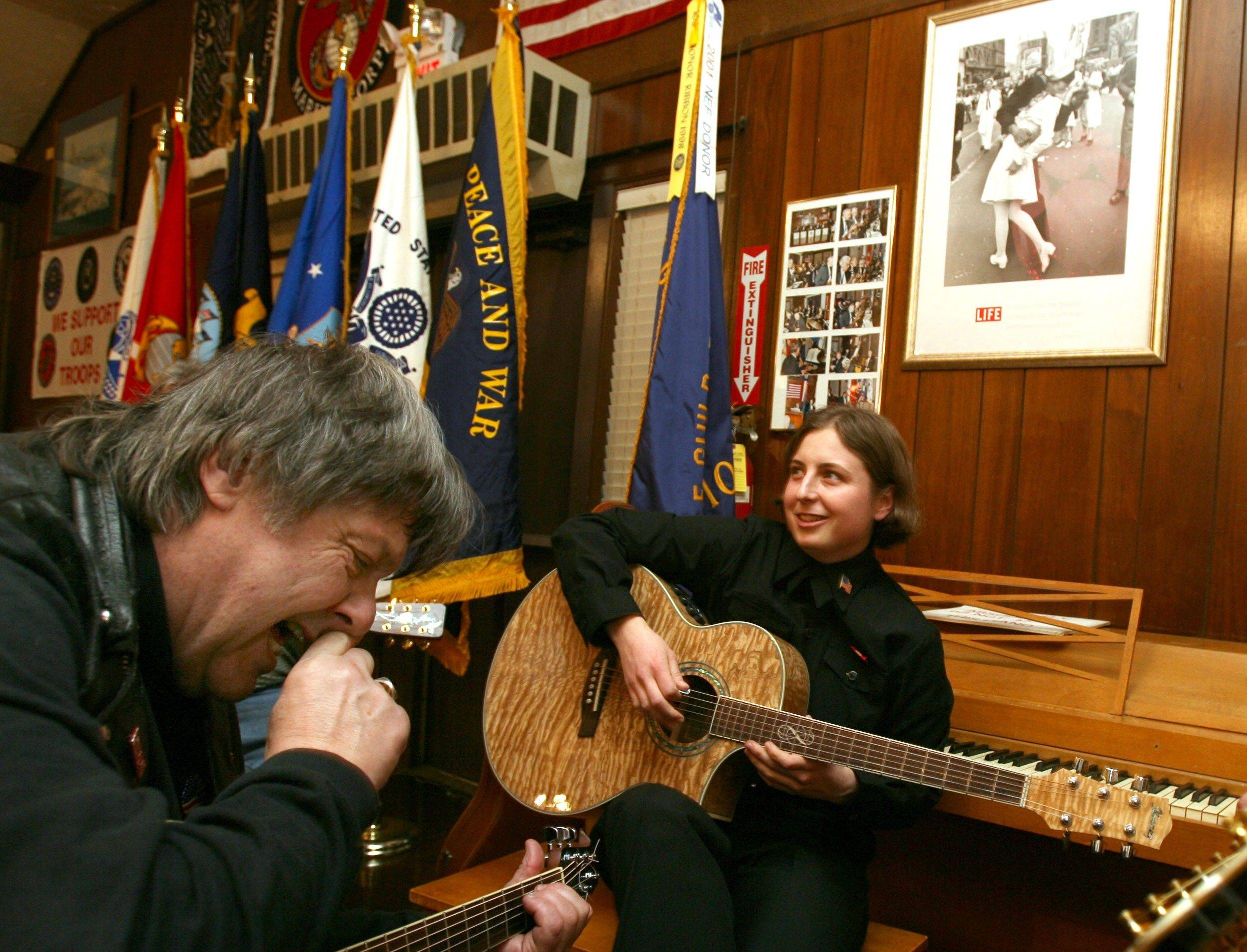 Ray Herr plays guitar with Great Lakes recruit Michelle Gray, following the 2006 Thanksgiving dinner at American Legion Post 208 in Arlington Heights.