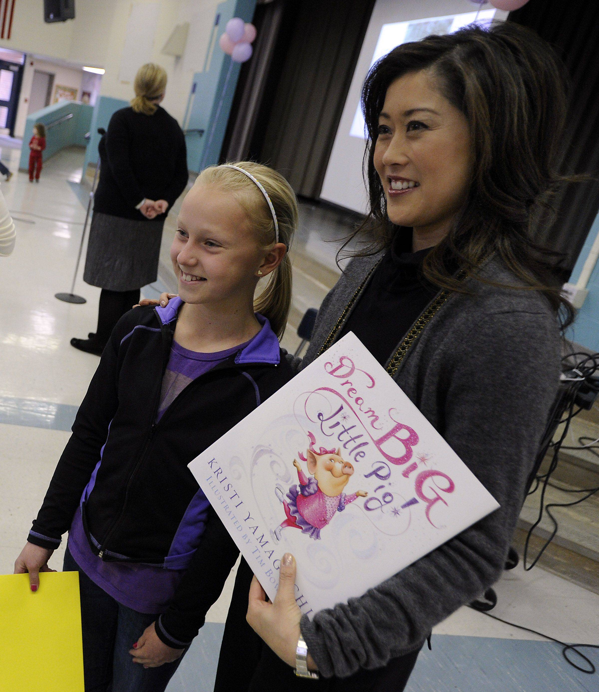 Olive-Mary Stitt student Claire Magnuson,10, gets her picture taken with Kristi Yamaguchi after she read her new children's book to the school on Tuesday.