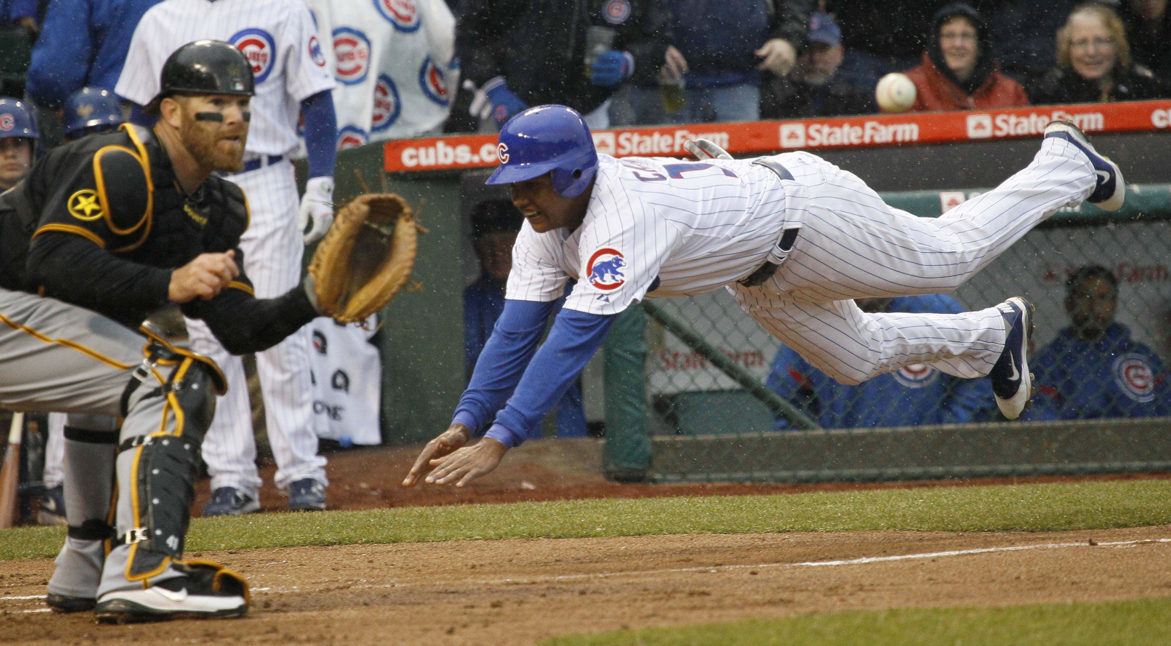 Cubs shortstop Starlin Castro, right, dives into home plates past Pittsburgh Pirates catcher Ryan Doumit, scoring off a throwing error by Pedro Alvarez, during the first inning Friday.