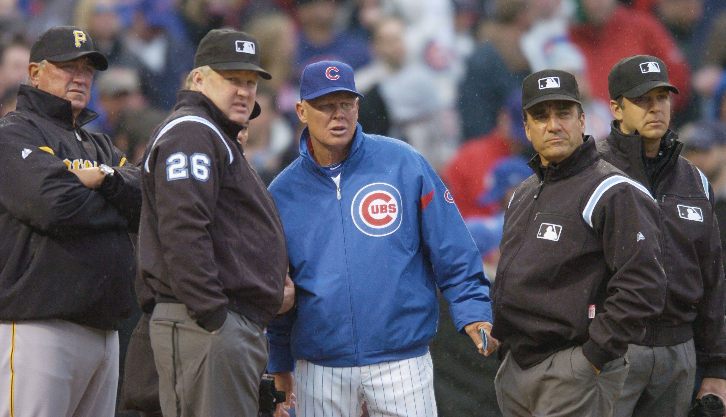 Cubs manager Mike Quade, middle, discusses the ground rules with the umpires and Pittsburgh manager Cint Hurdle prior to the game.