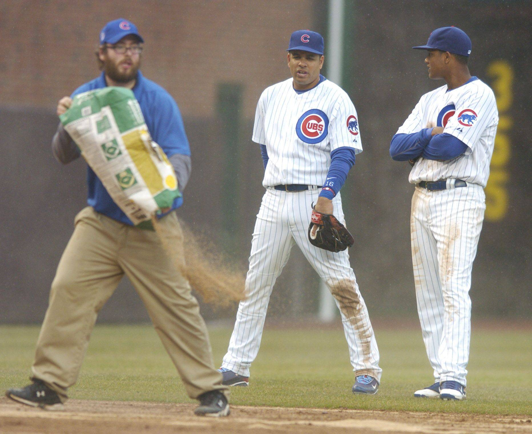 Cubs third baseman Aramis Ramirez, middle, and shortstop Starlin Castro chat as the grounds crew applies drying compound to the infield .
