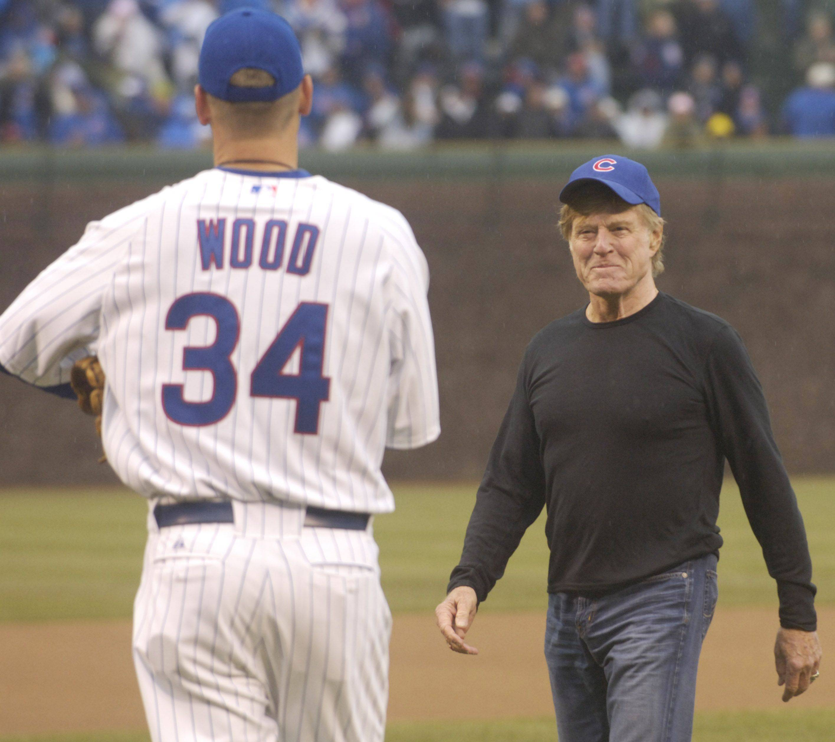 Actor and director Robert Redford walks to Kerry Wood after throwing out the first pitch.