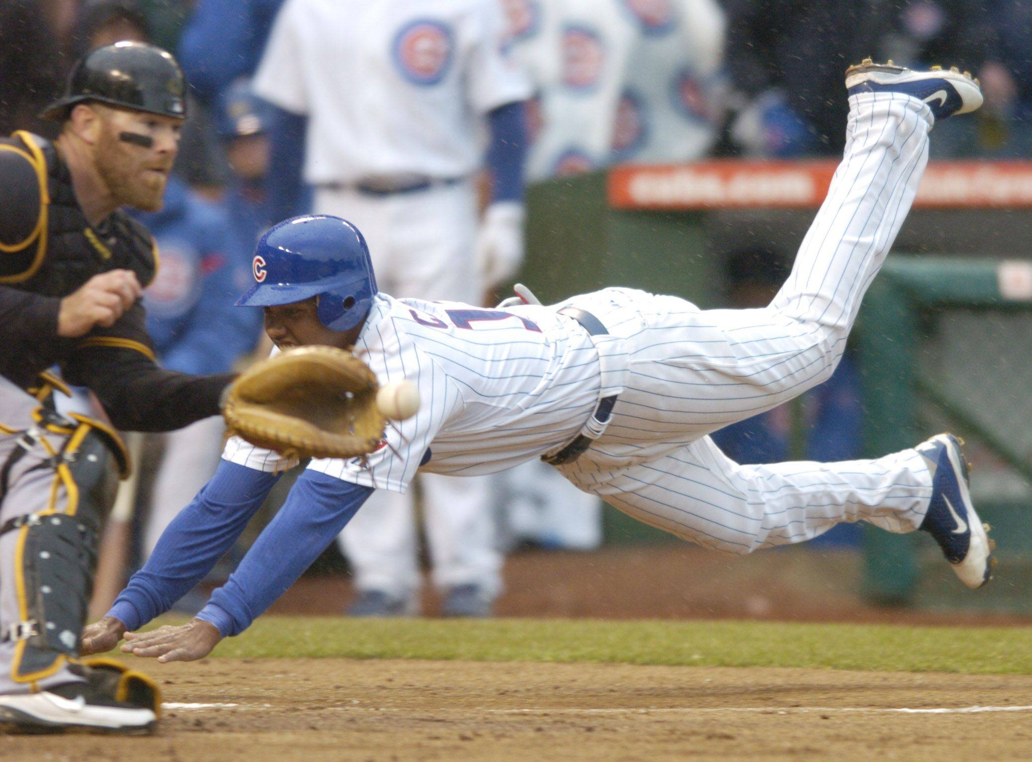 Starlin Castro of the Cubs dives past Pirates catcher Ryan Doumit during the first inning .