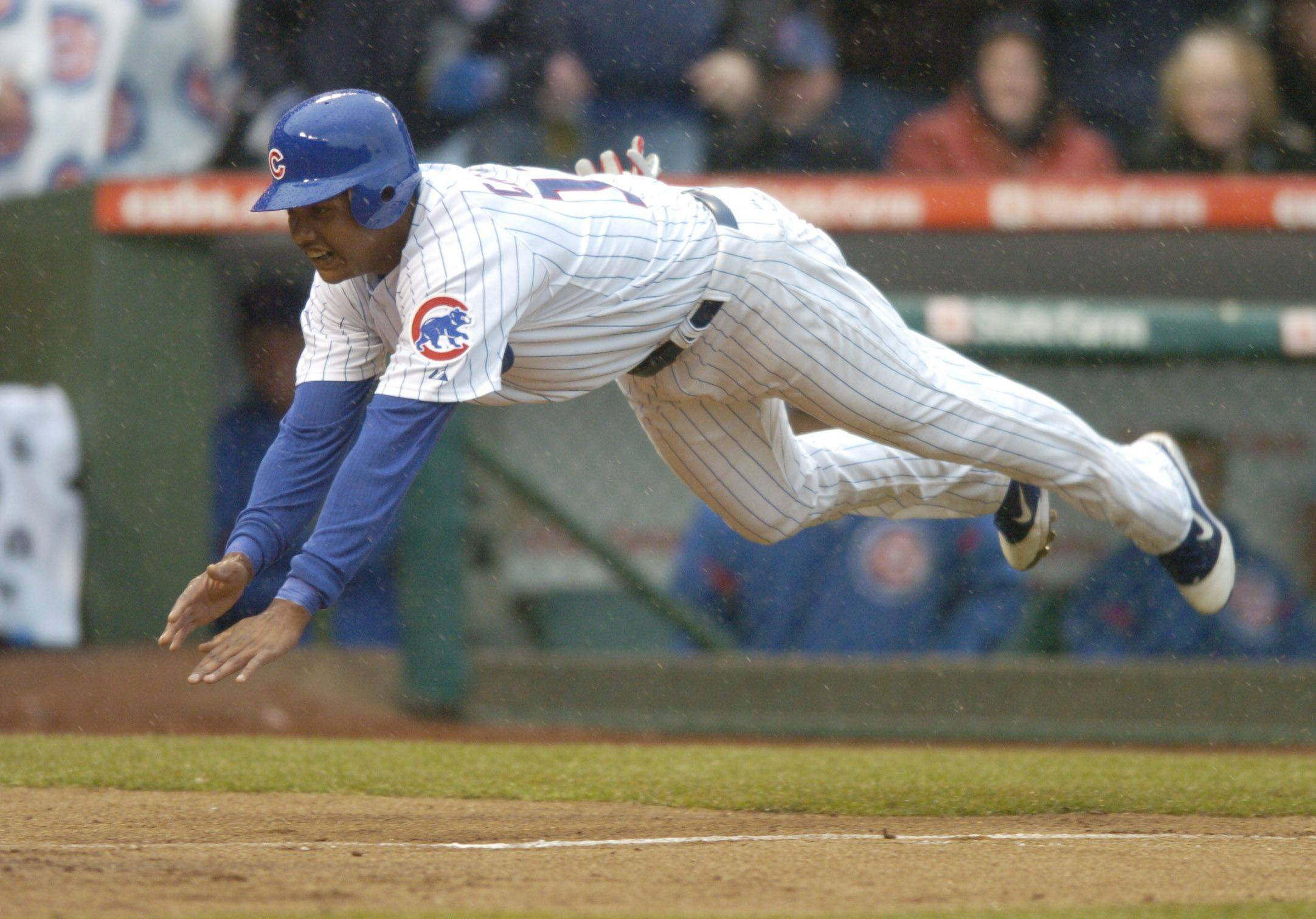 Starlin Castro of the Cubs dives toward the plate as he scores the game's first run .