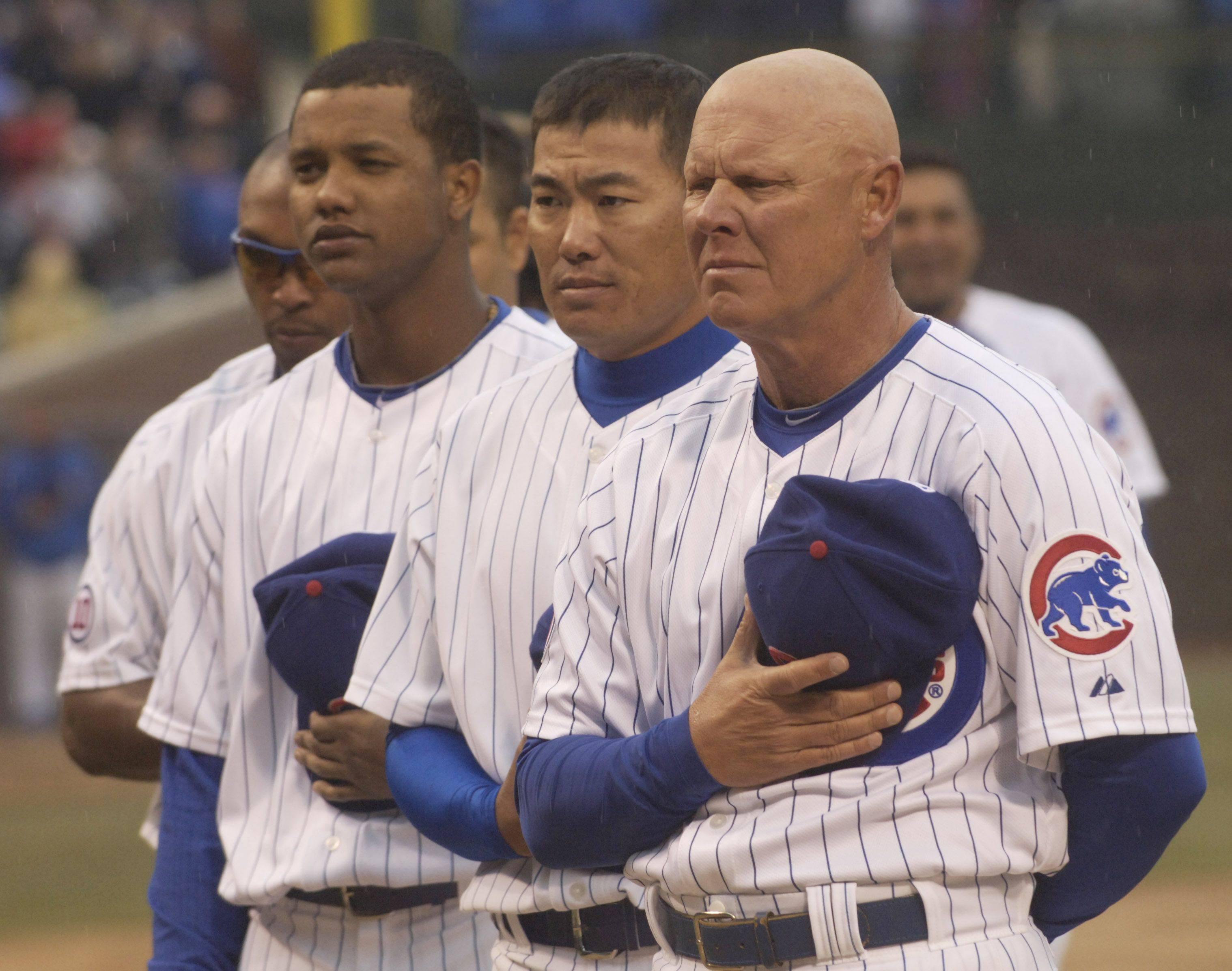 Cubs Manager Mike Quade stands with his team during the National Anthem.