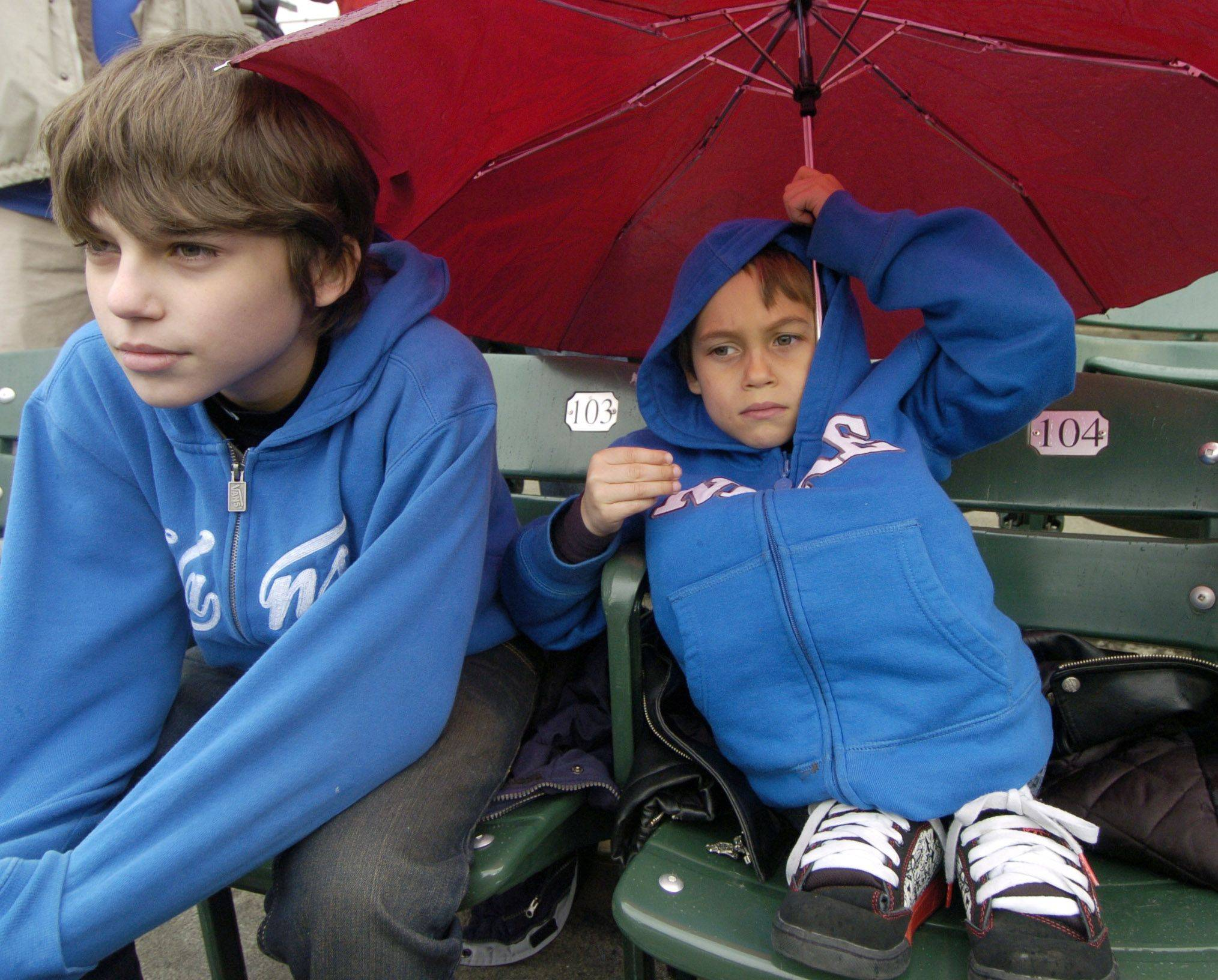 Adam Gilliam, 13, of Aurora, left, and his brother Zak, 6, try to stay warm and dry as they await the start of the game.