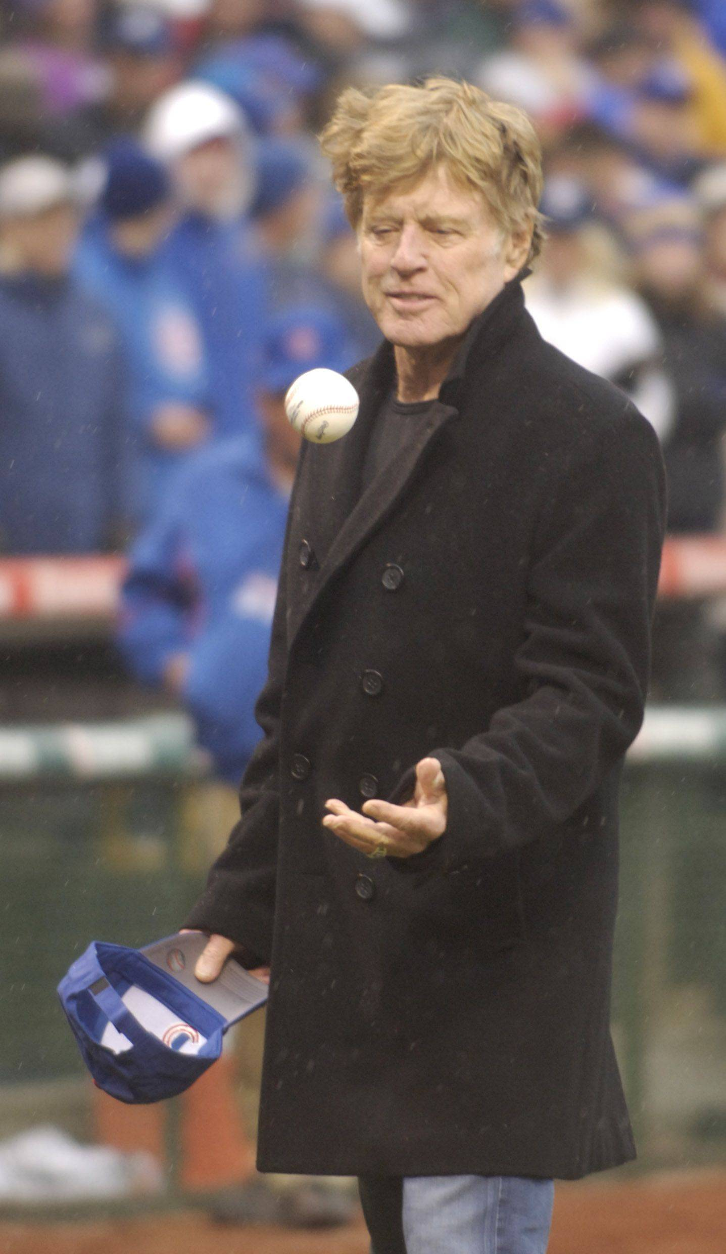 Actor and director Robert Redford flips the ball to himself prior to throwing out the first pitch .