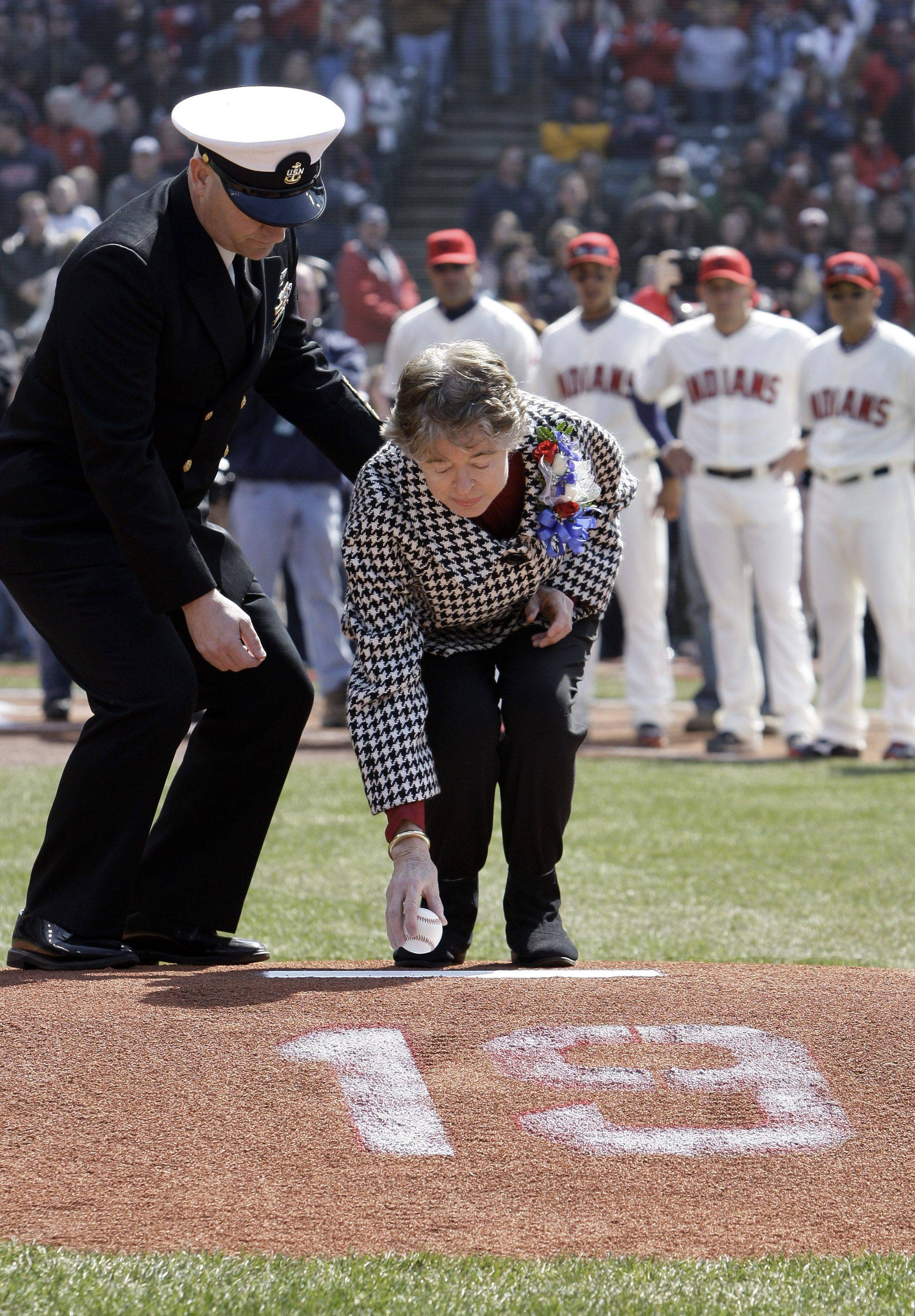 Anne Feller, wife of the late Cleveland Indians player Bob Feller, places a baseball on the mound before the Indians play the Chicago White Sox in an opening day baseball game on Friday, April 1, 2011, in Cleveland. Feller is assisted by Navy Chief Petty Officer Tod Green.