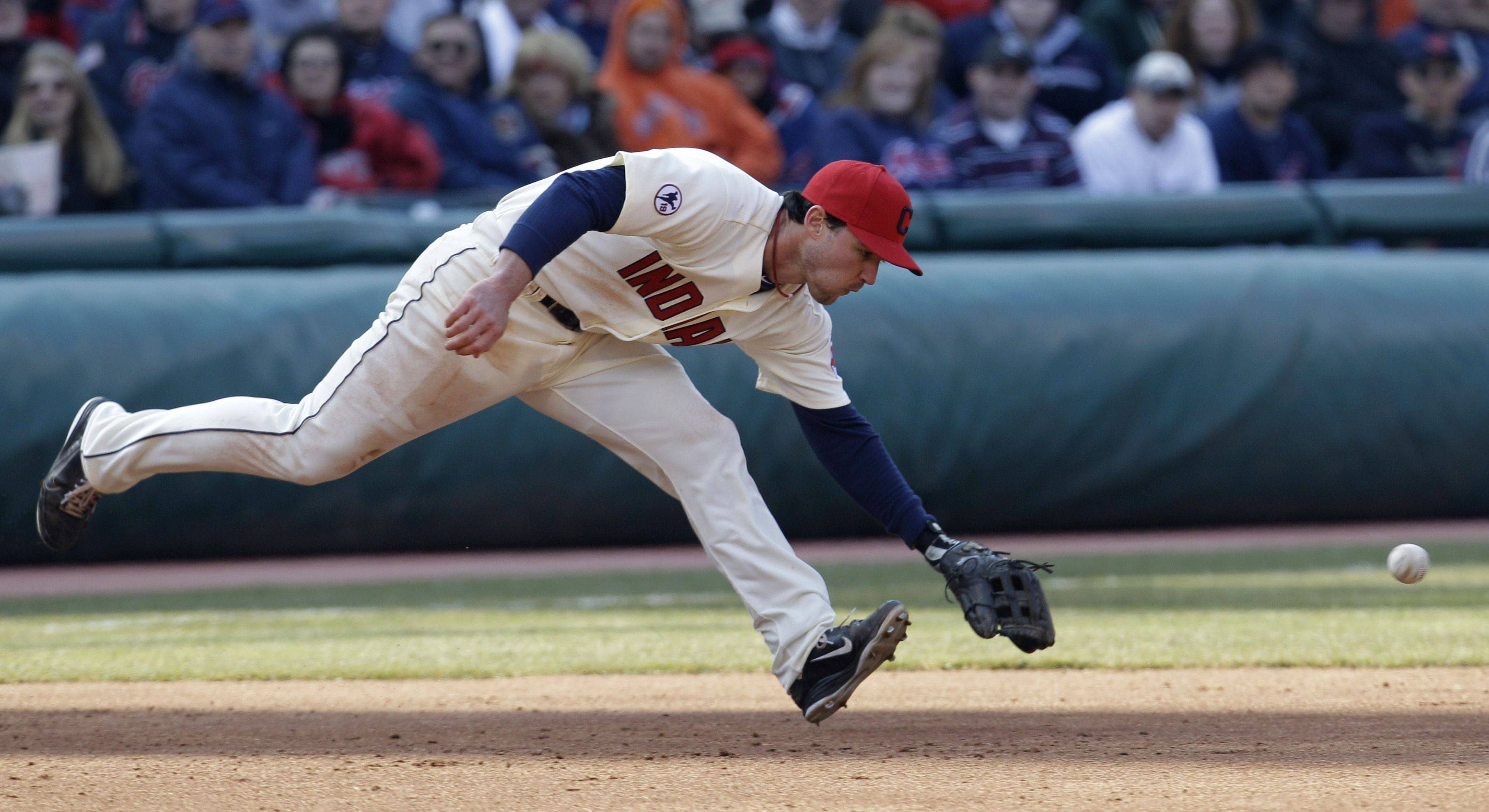 Cleveland Indians third baseman Jack Hannahan goes after a single hit by Chicago White Sox's Paul Konerko in the third inning in an opening day baseball game, Friday, April 1, 2011, in Cleveland.