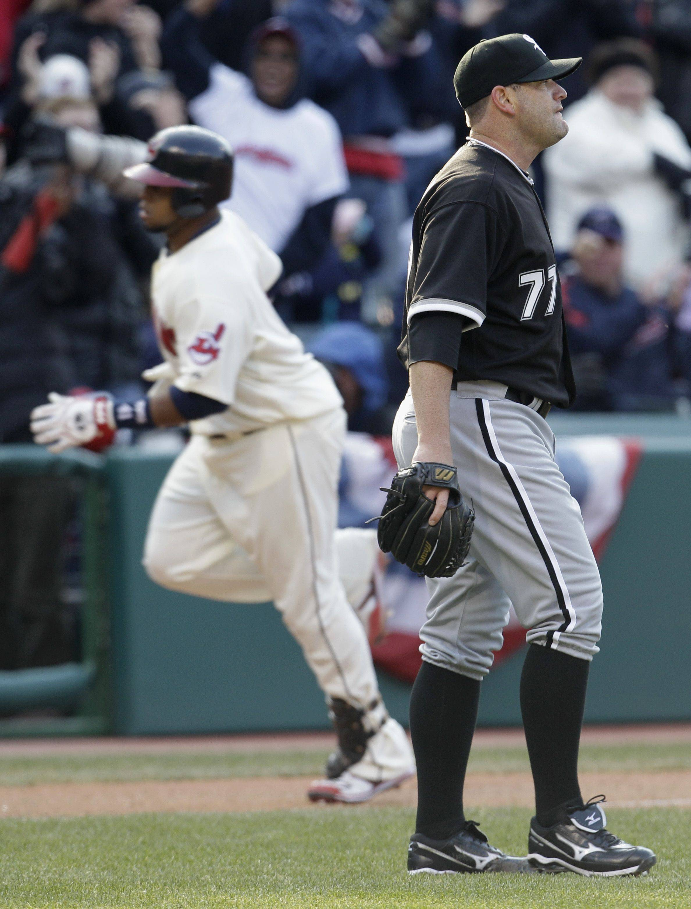 Chicago White Sox pitcher Will Ohman, right, reacts as Cleveland Indians catcher Carlos Santana runs the bases after Santana hit a two-run home run in the seventh inning in an opening day baseball game on Friday, April 1, 2011, in Cleveland. Asdrubal Cabrera also scored.