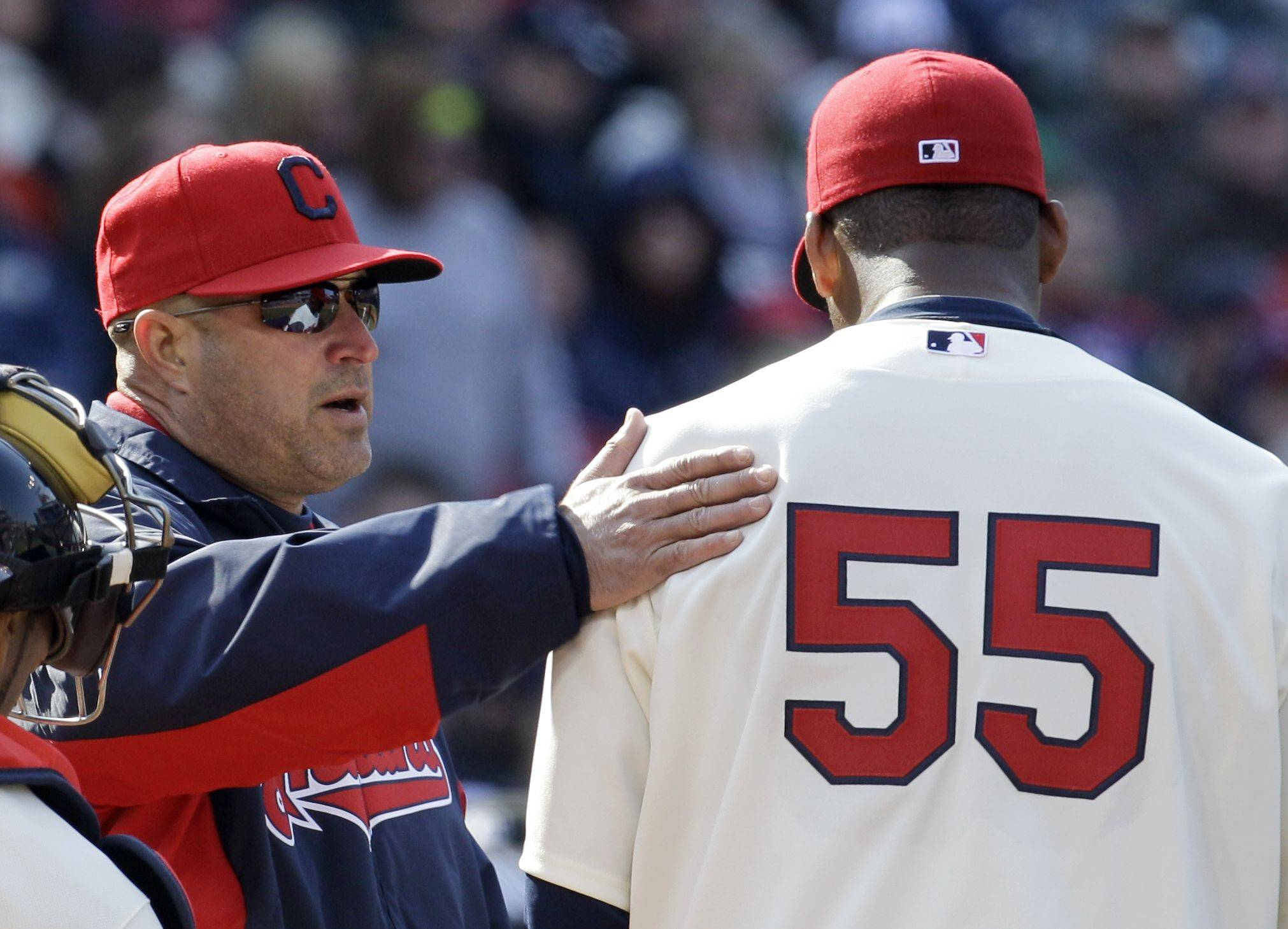 Cleveland Indians manager Manny Acta, left, pats Indians starting pitcher Fausto Carmona on the shoulder in the fourth inning in an opening day baseball game against the Chicago White Sox, Friday, April 1, 2011, in Cleveland. Carmona left the game in the fourth inning.