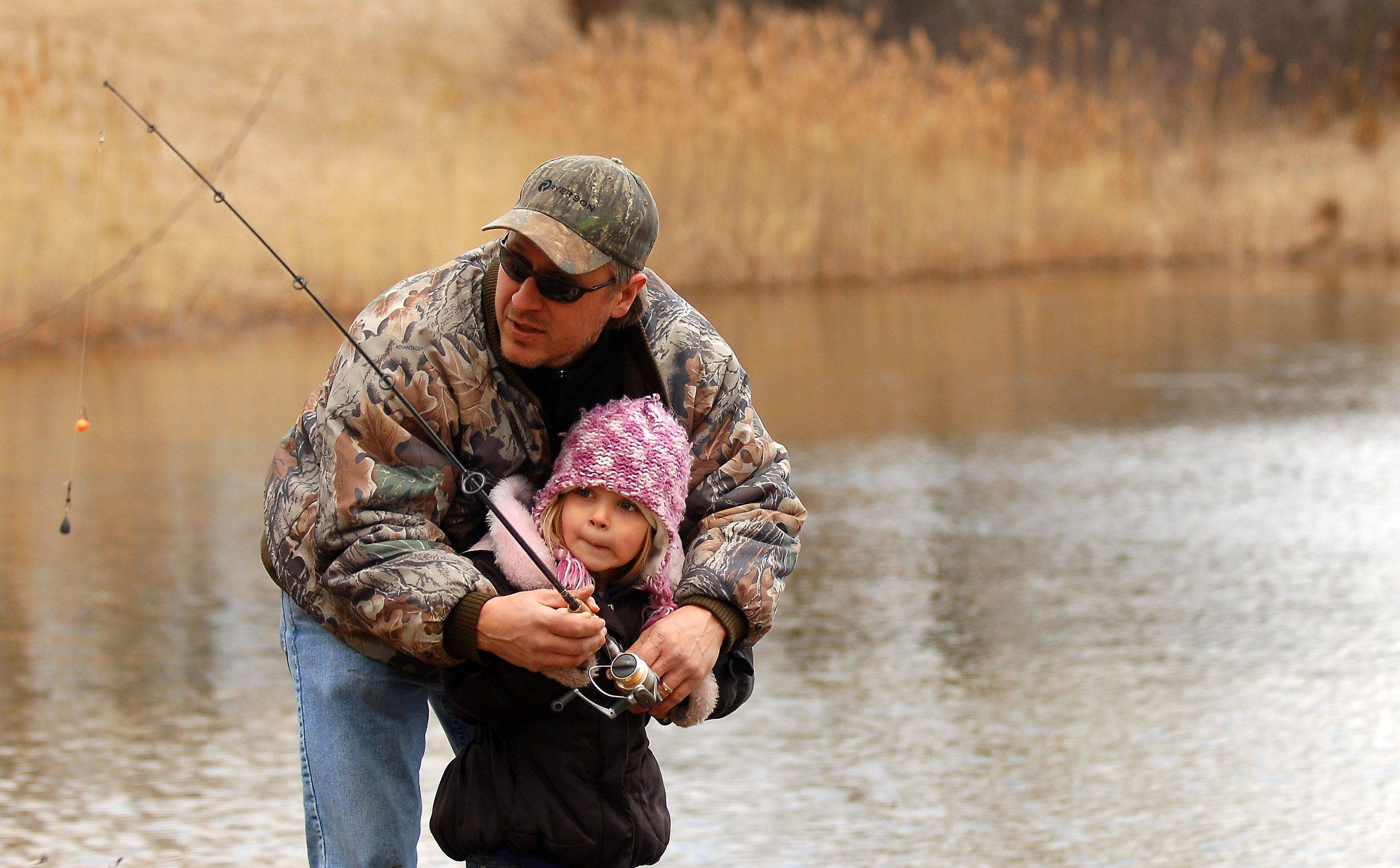 Scott Brown of Island Lake helps his daughter, Haley, 5, cast during the opening of trout fishing season Saturday at Lake Atwood, in the Hollows Conservation Area in Cary. The McHenry County Conservation District stocked more than 2,000 rainbow trout in the lake. Haley's brother Nathan, 7, also was in on the fishing action.