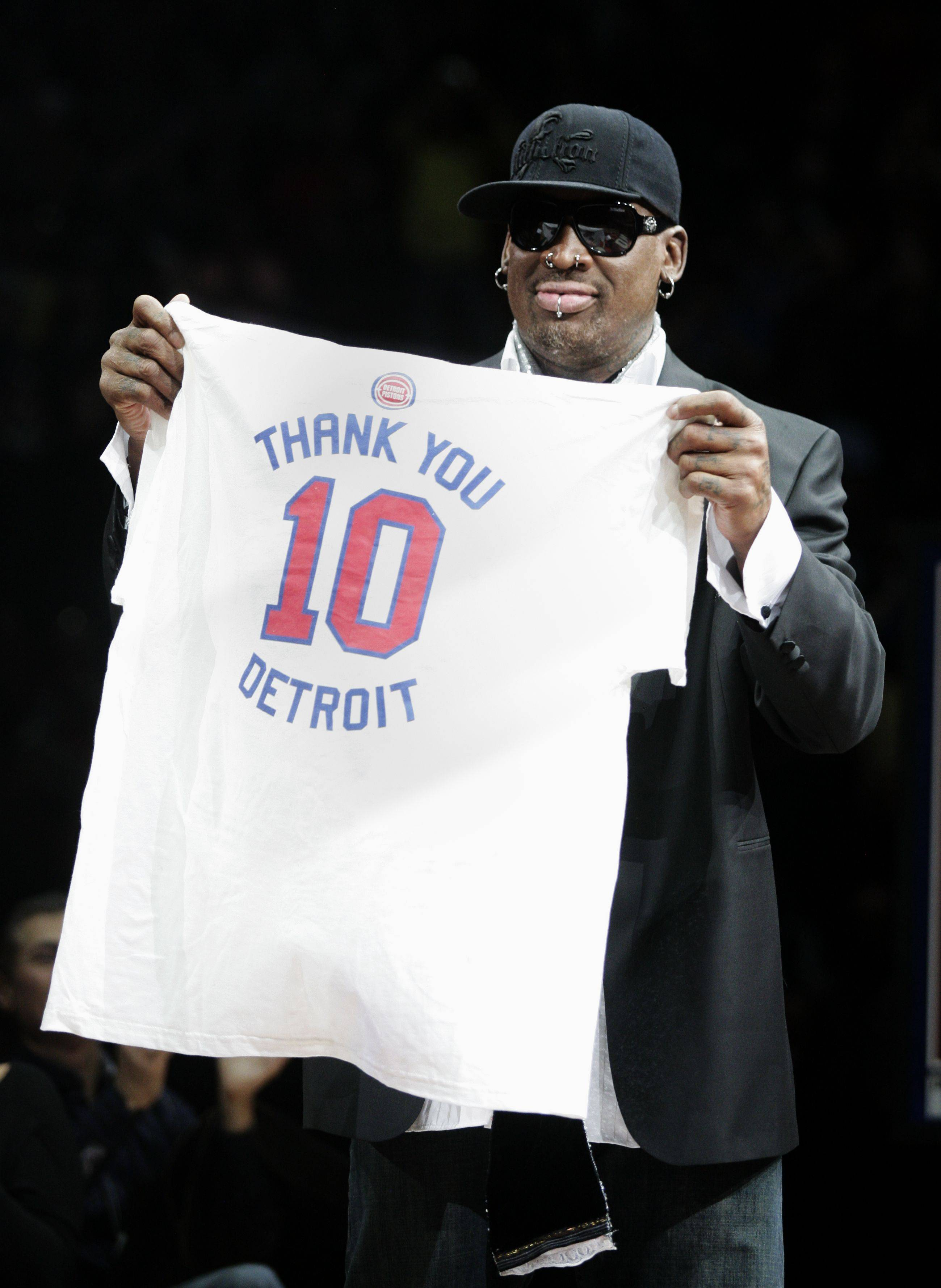 Former Detroit Piston Dennis Rodman holds up a t-short with his number 10 to thank the fans during a ceremony to retire his jersey at an NBA basketball game against the Chicago Bulls Friday, April 1, 2011, in Auburn Hills, Mich.