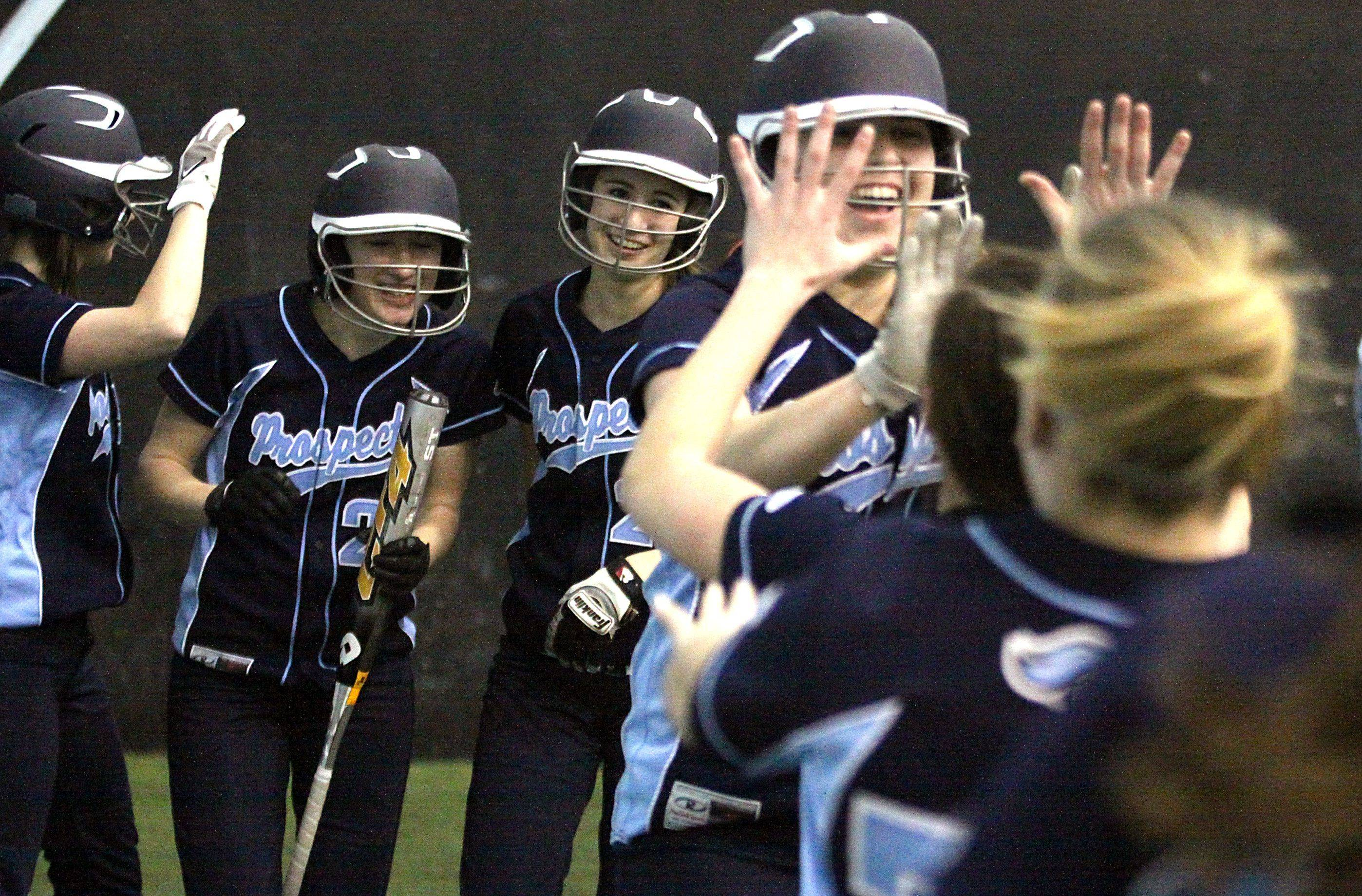 Prospect's Michele Molini, from left, Amy Graham and Mary Styzek of Prospect watch as teammate Nicole Surico is congratulated after a home run against Libertyville during Monday's game at the Sports Center in Schaumburg.