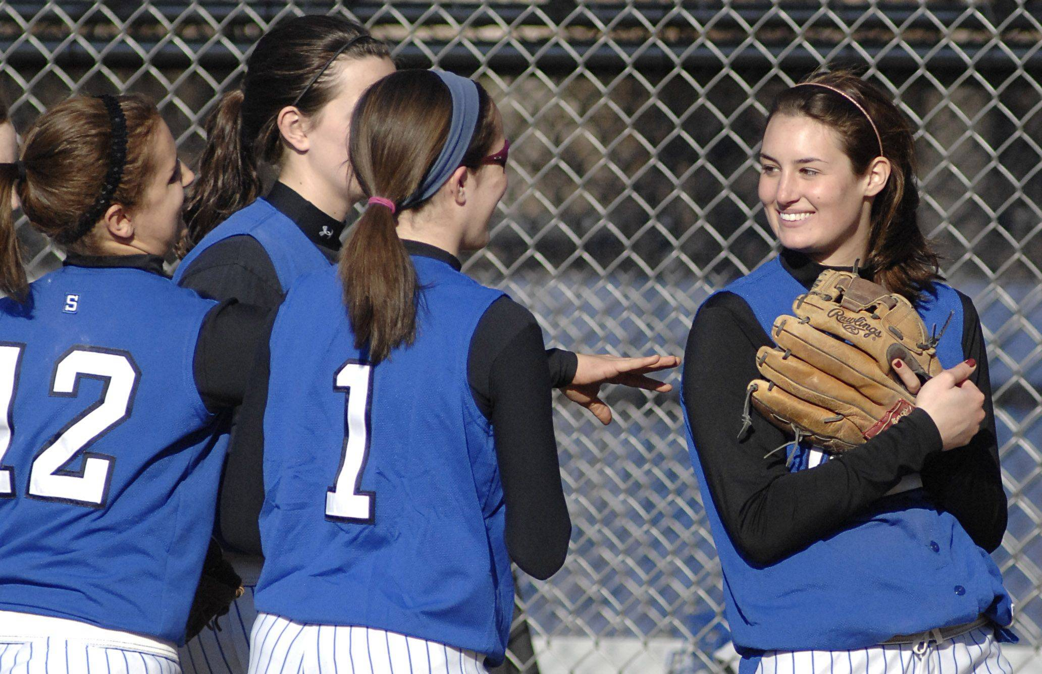 Geneva's Kelly McCaffrey smiles as teammates cheer her on for catching the final out of the seventh inning to seal their win over St. Francis on Wednesday, March 30.