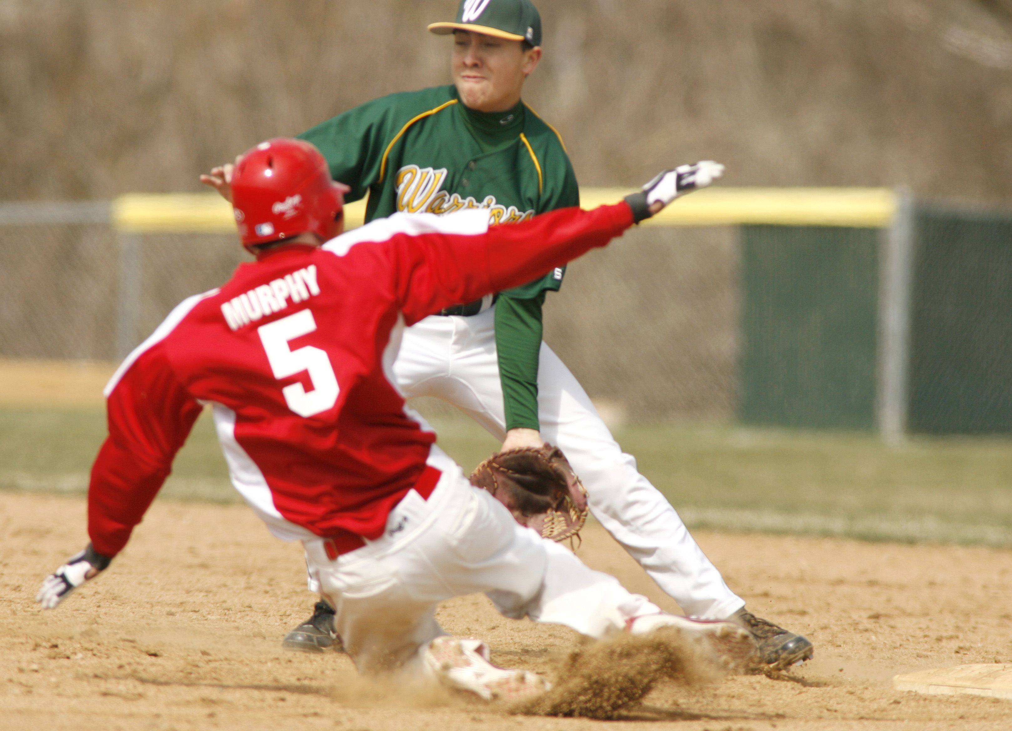 Naperville Central High School's Ross Murphy (5) slides safely into second base against Waubonsie Valley High School's Ryan Vega during boys baseball action at Waubonsie Valley.